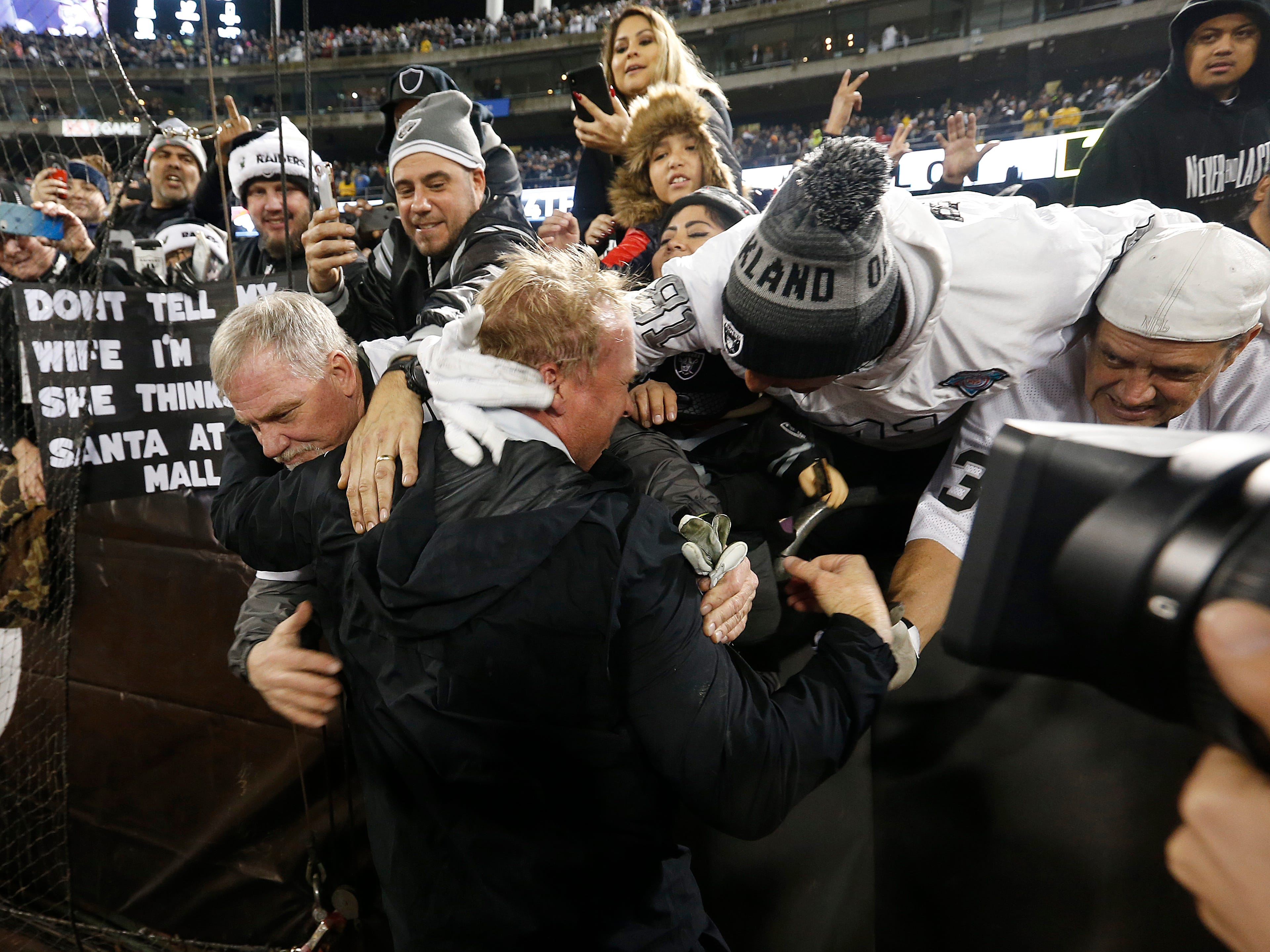 Raiders head coach Jon Gruden hugs fans after Monday night's game against the Denver Broncos in Oakland.