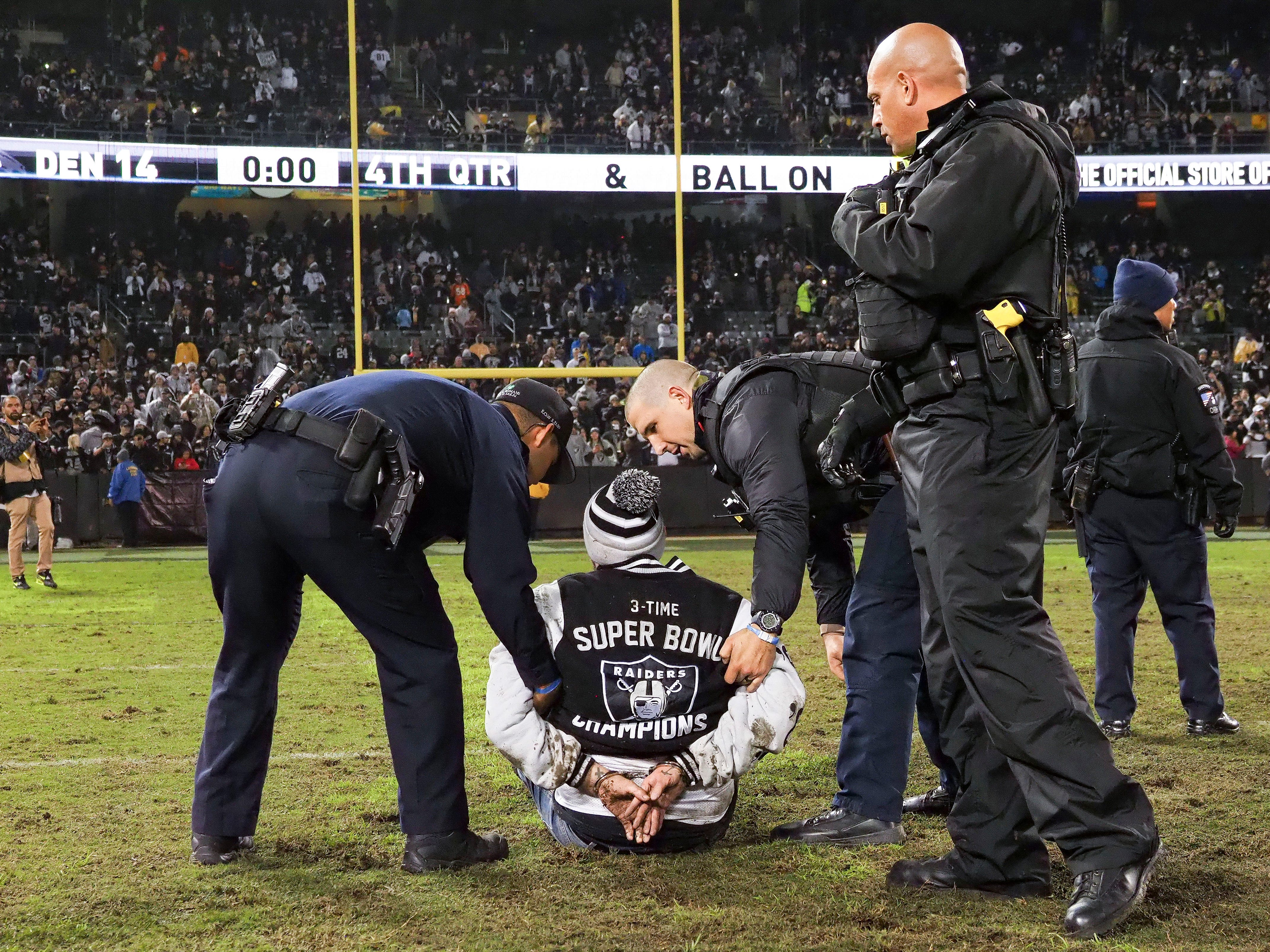 An Oakland Raiders fan is handcuffed after rushing the field after the game against the Denver Broncos at Oakland Coliseum.