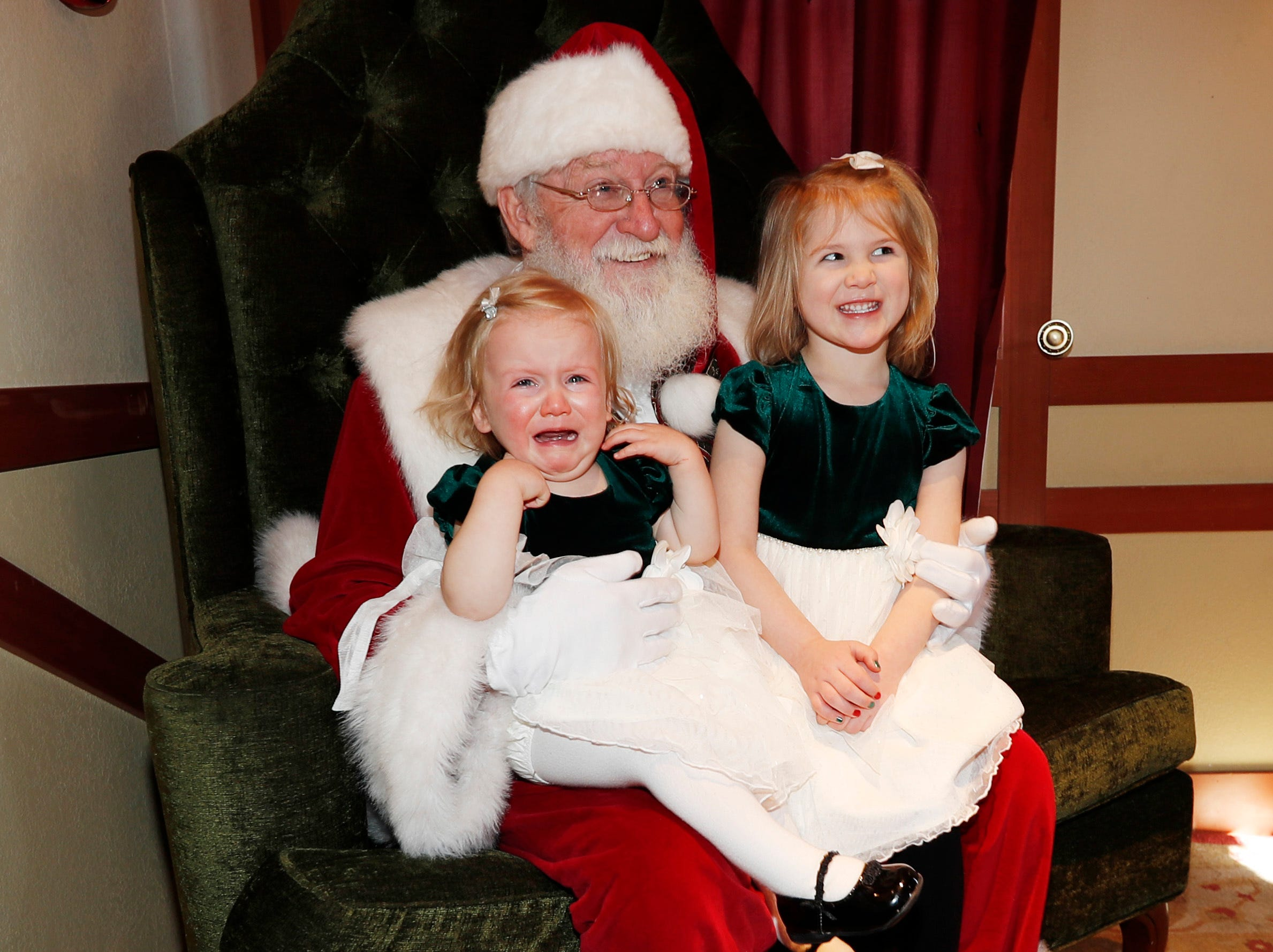 Eighteen-month-old Briell Digiacom of Lone Tree, Colo., expresses her dislike of posing for a photograph with Santa Claus with her 4-year-old sister, Keri, as last-minute shoppers finish up their Christmas gift lists at the Outlet Malls in Castle Rock Monday, Dec. 24, 2018, in Castle Rock, Colo. Retailers were offering ample discounts plus even more price cuts to those shoppers who ventured out with the holiday looming.