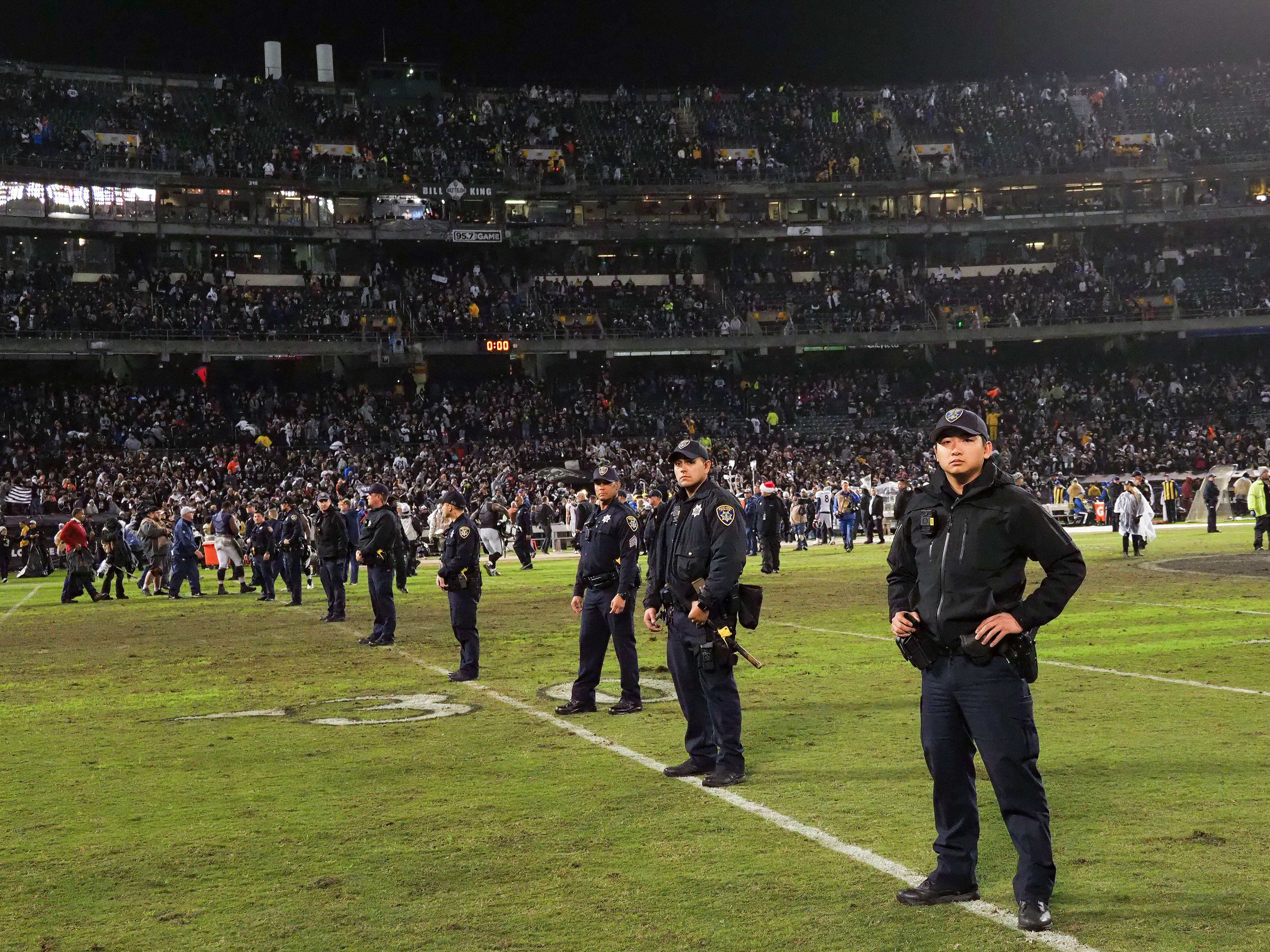 Police presence on the field after the Oakland Raiders' 27-14 win over the Denver Broncos in what might be the final NFL game at the Oakland Coliseum.