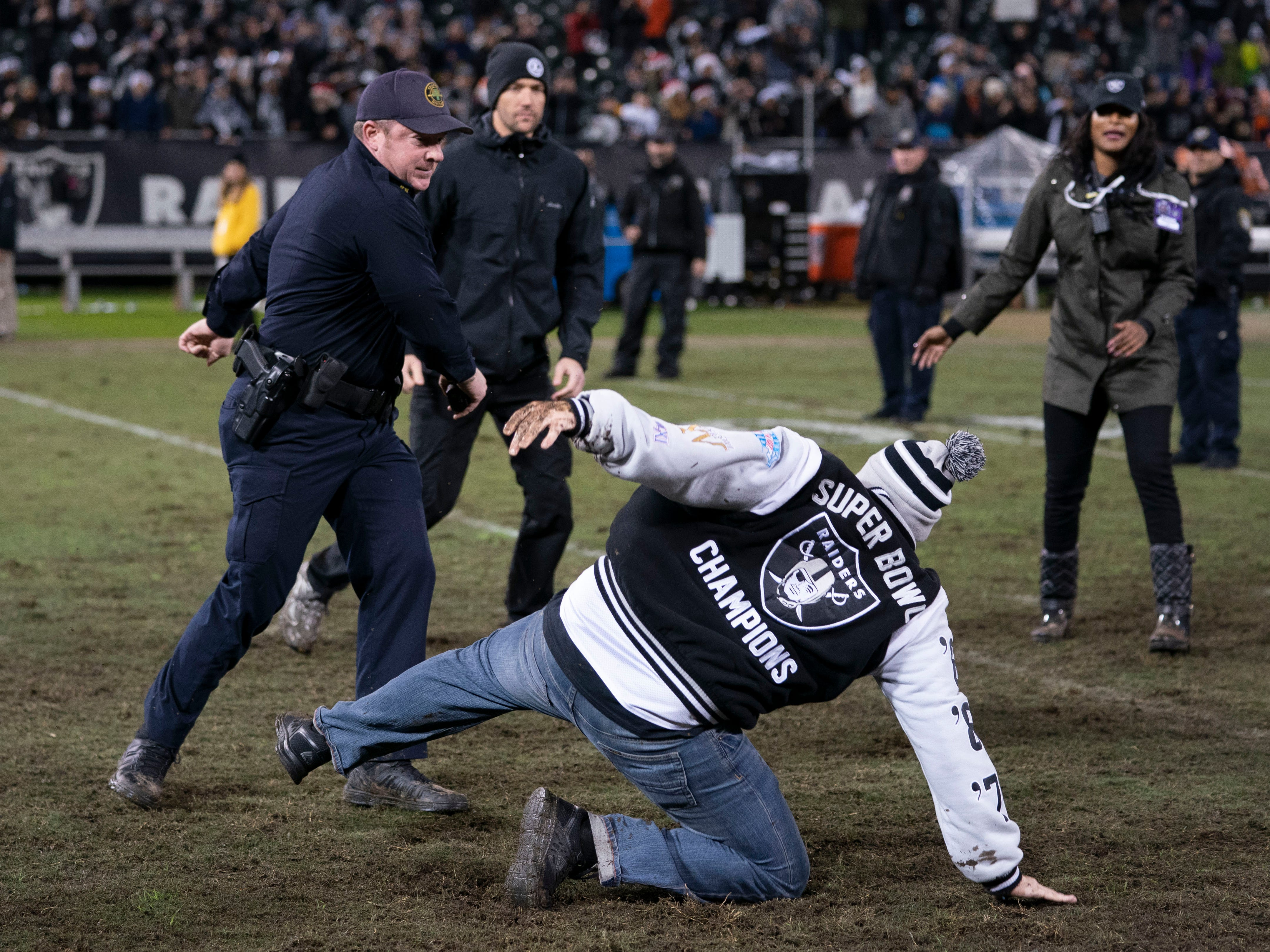 An Oakland Raiders fan runs onto the field after the game against the Denver Broncos at Oakland Coliseum.