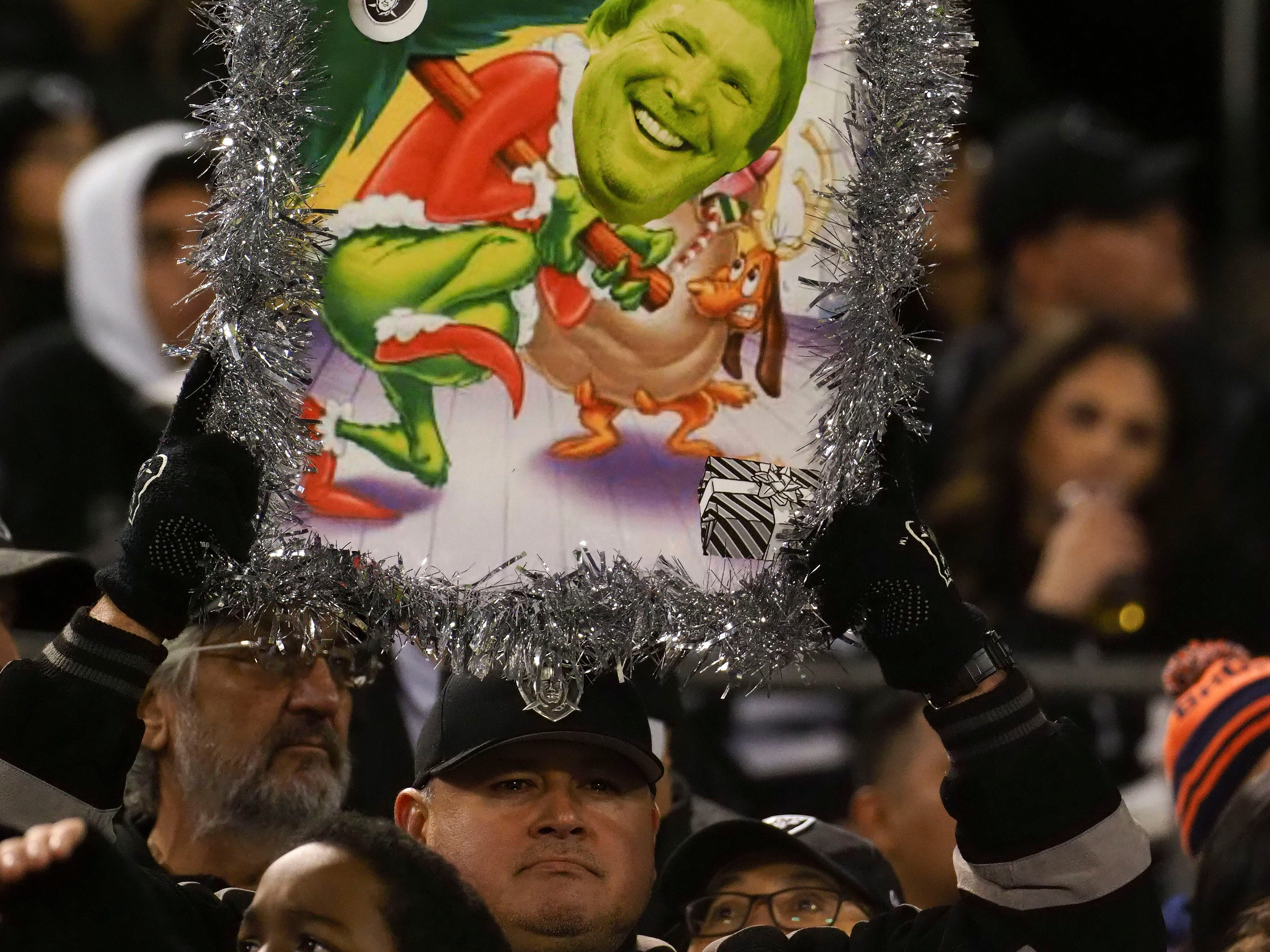 "An Oakland Raiders fan holds a signed reading ""How the Grinch stole the Raiders from Oakland"" with a photo of team owner Mark Davis."