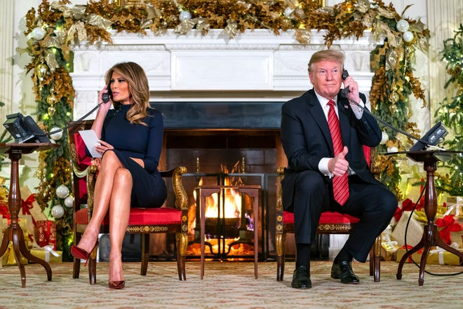 President Donald J. Trump (R) and First Lady Melania (L) speak with children who are calling the NORAD (North American Aerospace Defense Command) Santa tracker in the State Dining Room of the White House in Washington, DC, on Dec. 24. 2018. Earlier in the day, President Trump tweeted that he was 'all alone in the White House' waiting for Democrats to make a deal on border security. Though President Trump said he was 'proud' to shut the government down, lawmakers will meet again later this week to attempt to negotiate a way around the stalemate.