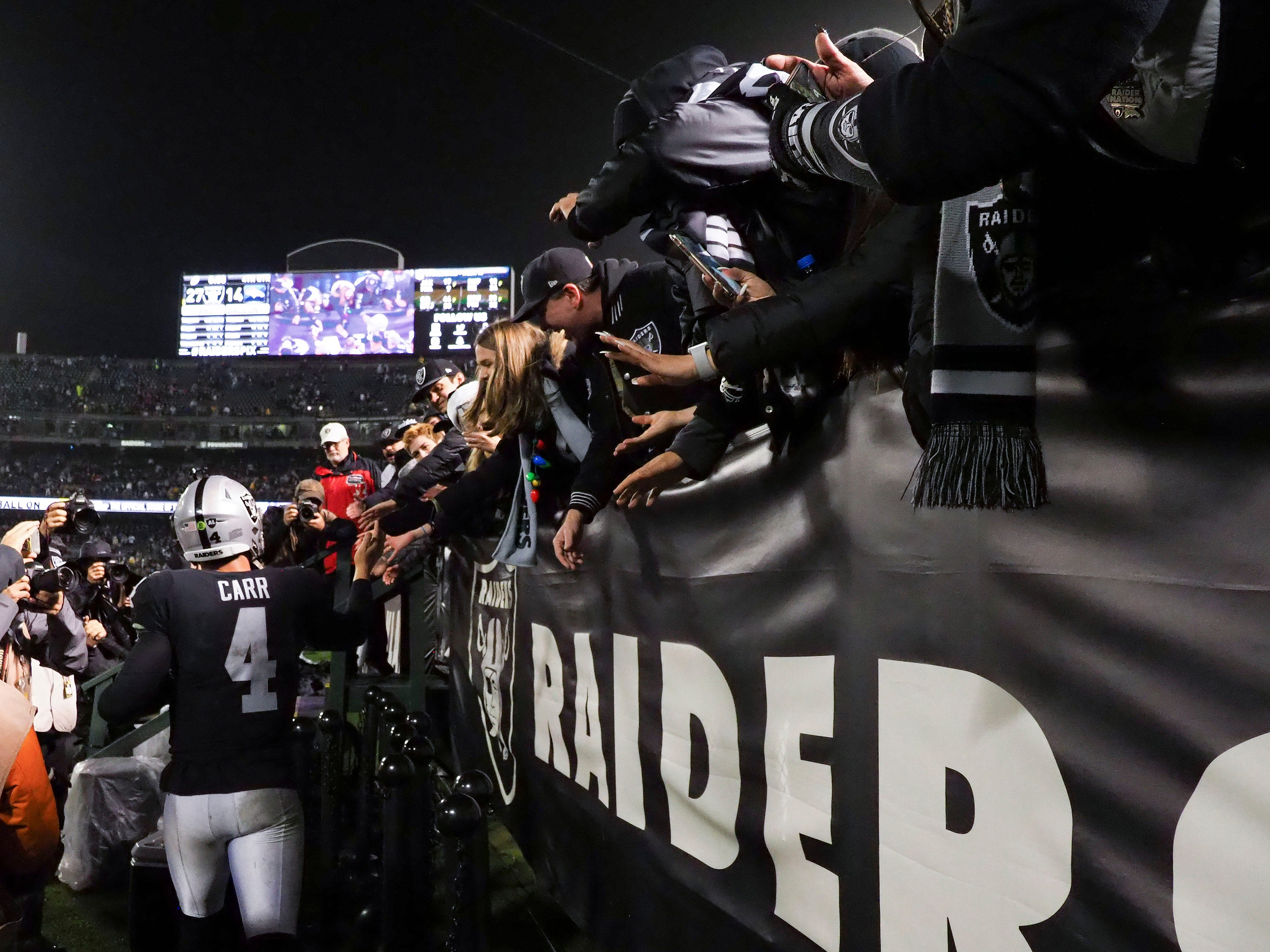 Raiders quarterback Derek Carr walks the perimeter of the field to high-five fans after the game against the Denver Broncos at Oakland Coliseum.