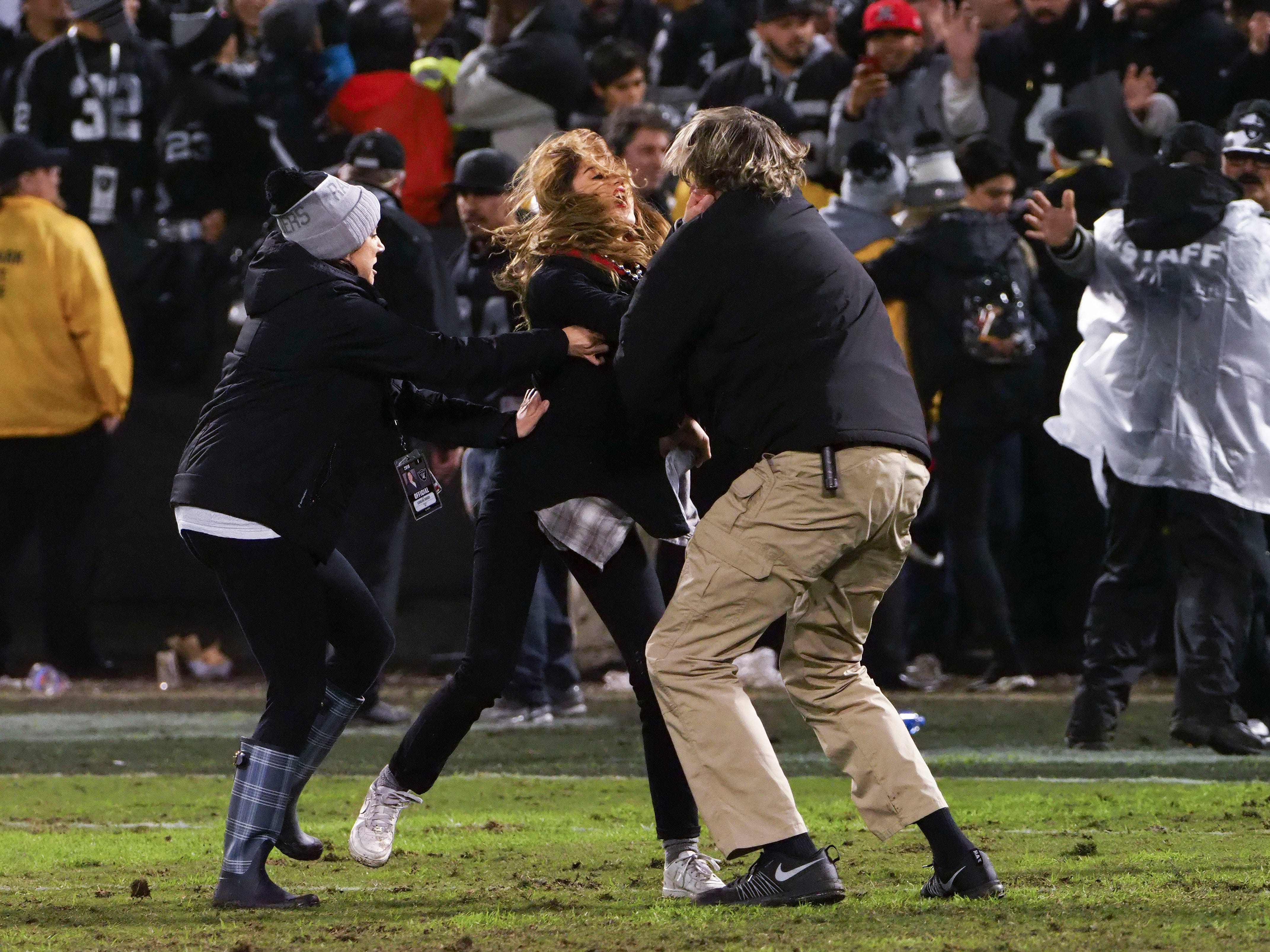 Security personnel try to control a fan who rushed the field after the game between the Oakland Raiders and the Denver Broncos at Oakland Coliseum.