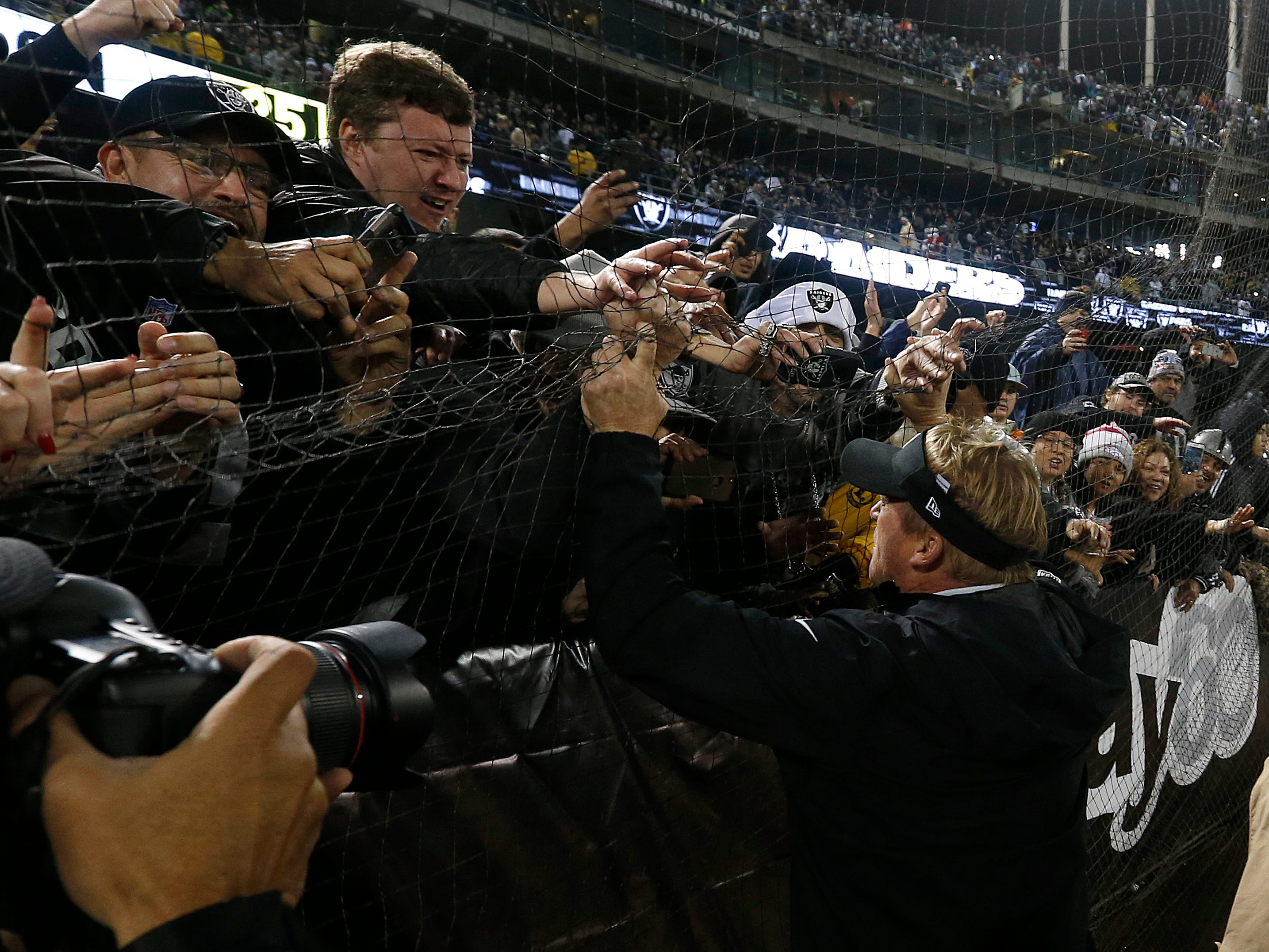 Oakland Raiders head coach Jon Gruden greets fans after Monday night's  against the Denver Broncos in Oakland.