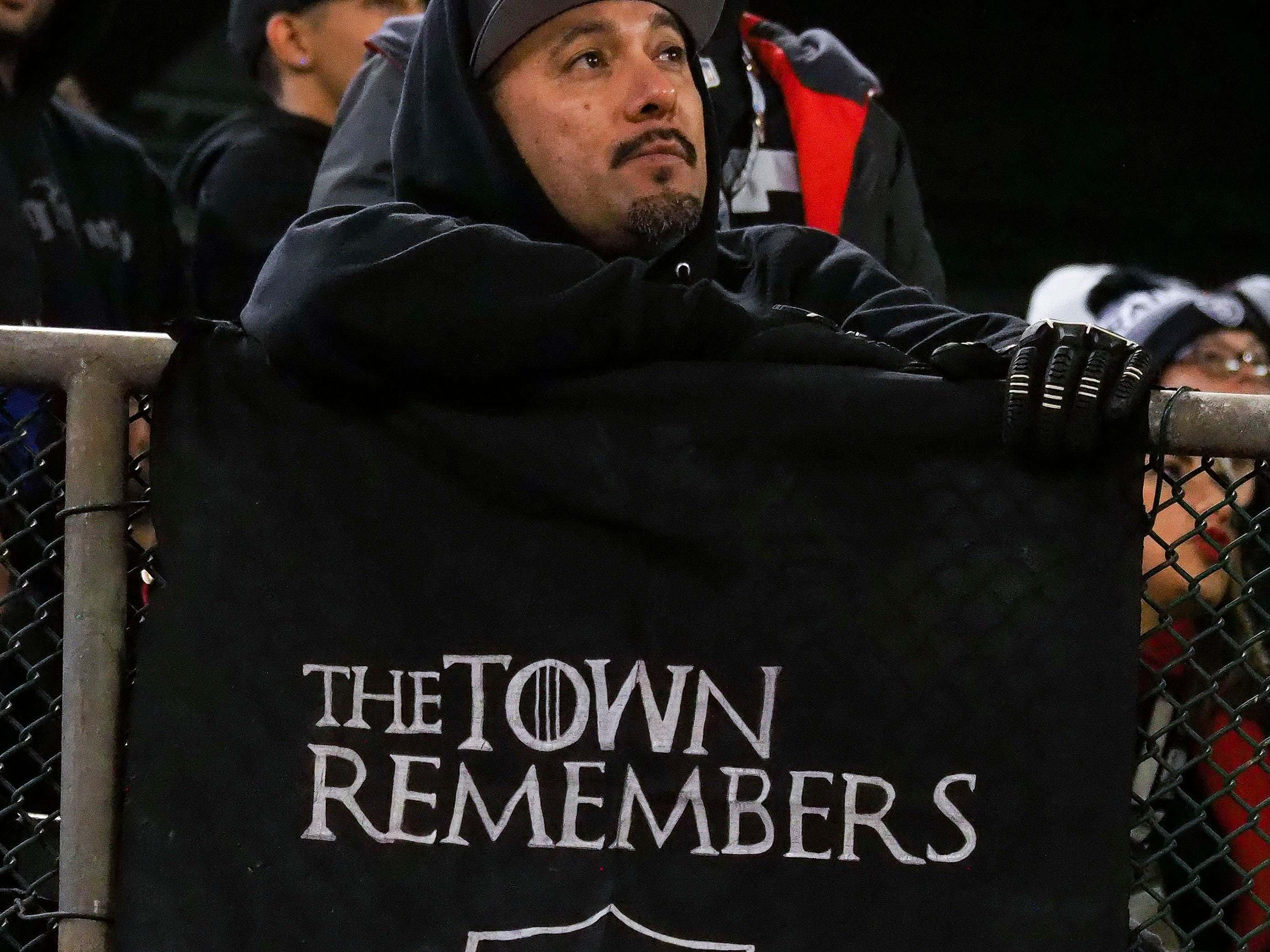 "An Oakland Raiders fan holds a banner reading ""The Town Remembers"" at the Oakland Coliseum."