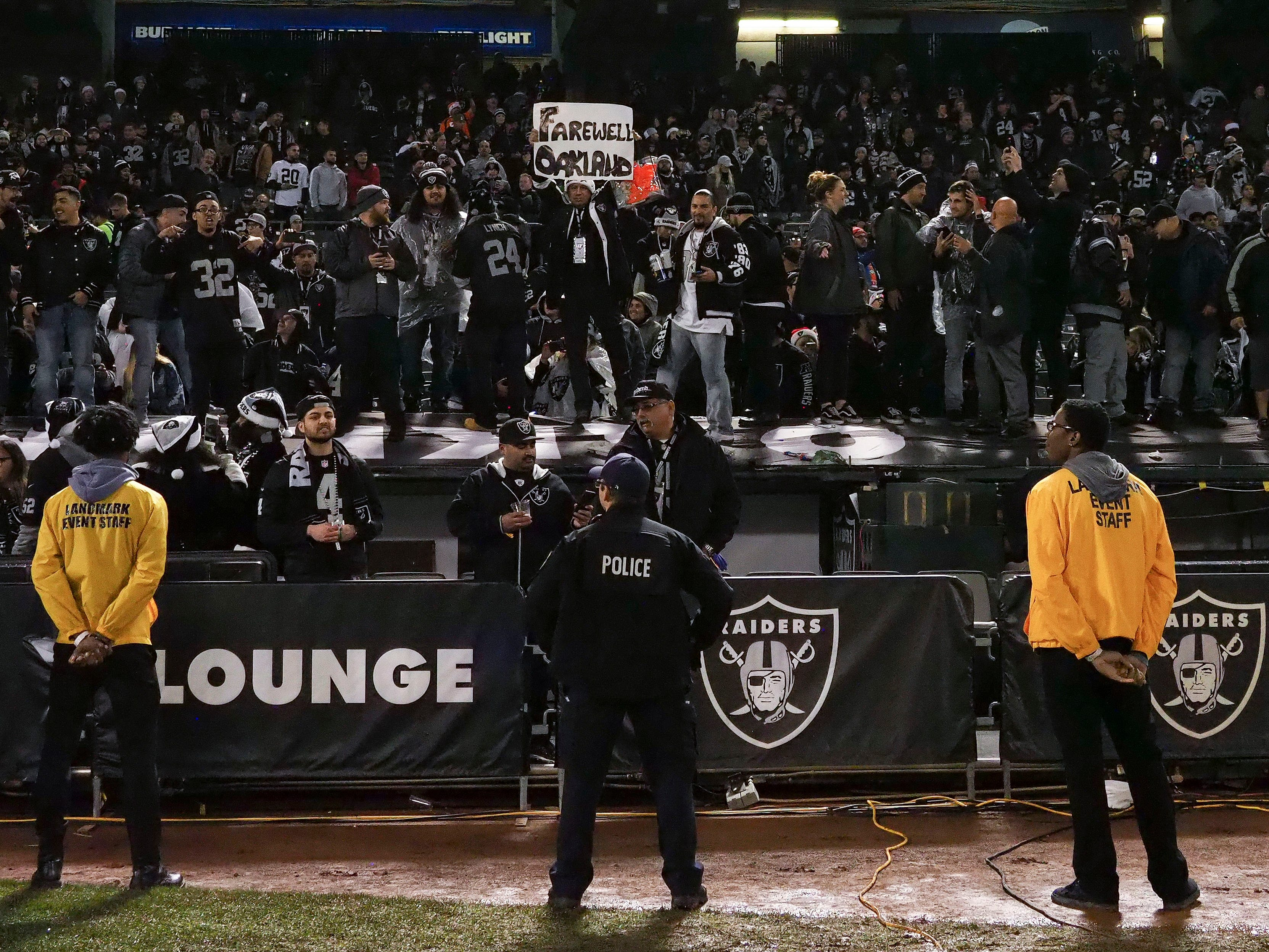 Raiders fans stand on top of the dugout after the game against the Denver Broncos at Oakland Coliseum.