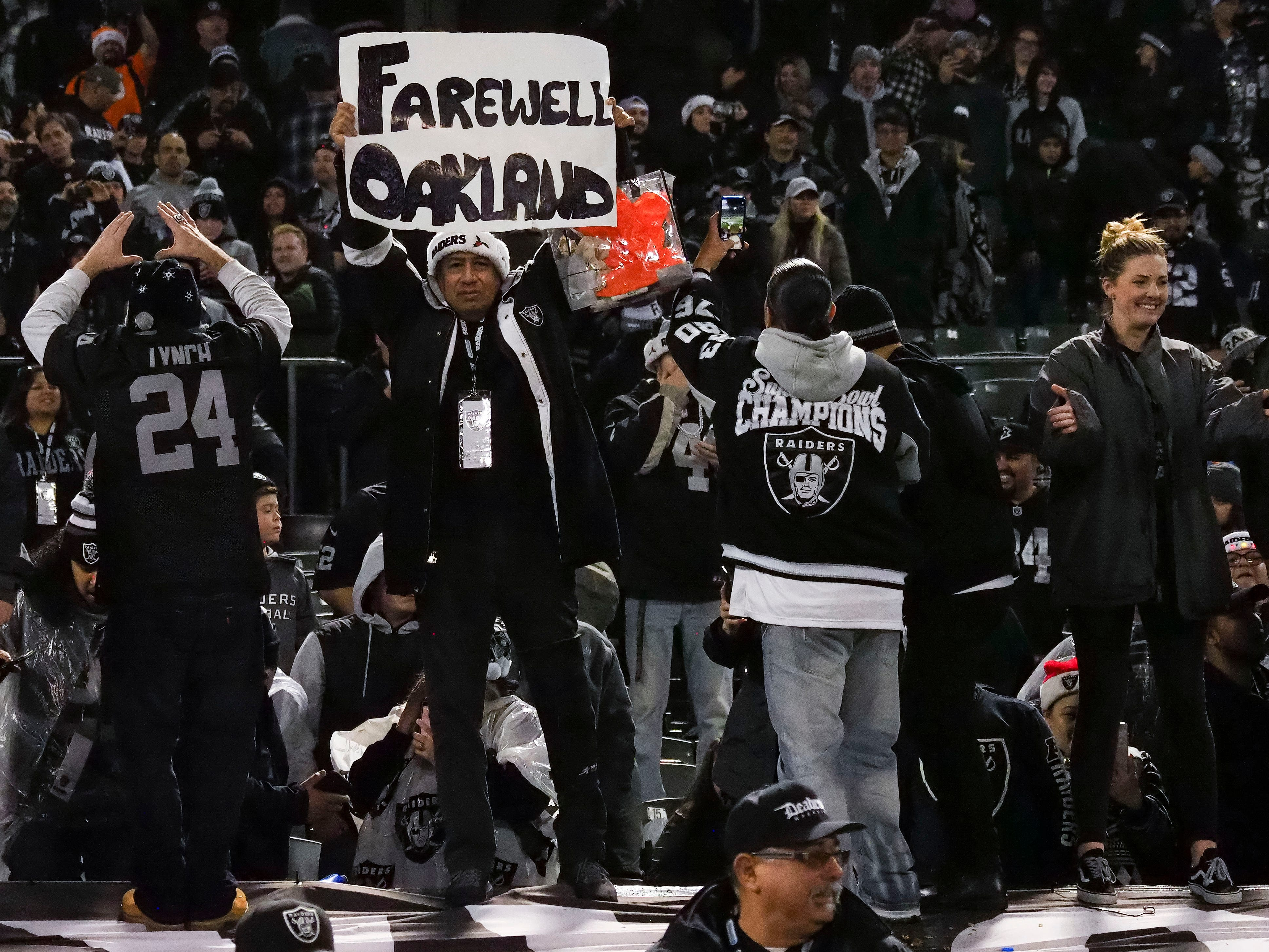 "An Oakland Raiders fan holds a sign reading ""Farewell Oakland"" after the game against the Denver Broncos at Oakland Coliseum."
