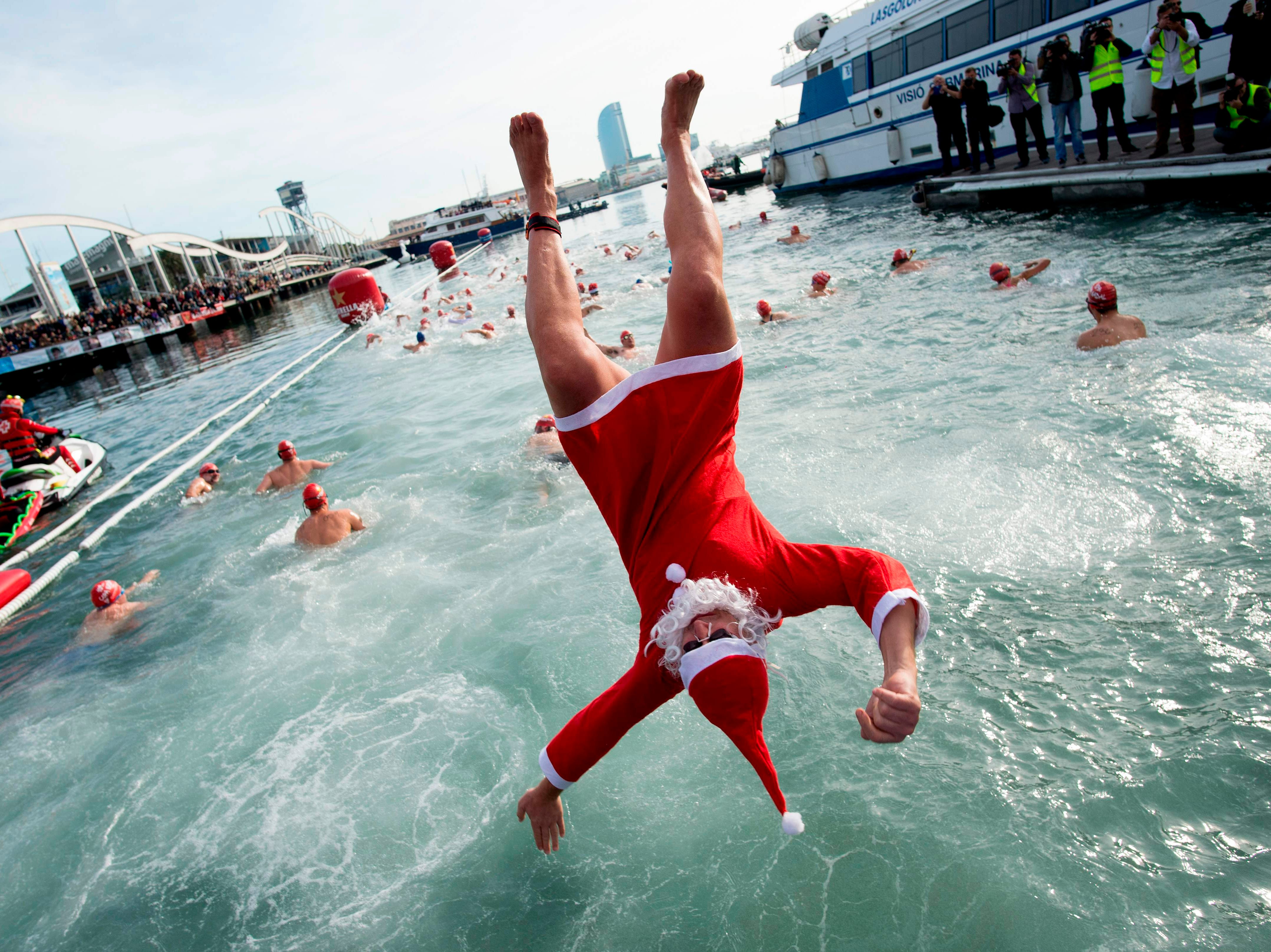 A participant in a Santa Claus costume jumps into the water during the 109th edition of the 'Copa Nadal' (Christmas Cup) swimming competition in Barcelona's Port Vell on Dec. 25, 2018.  The traditional 200-meter Christmas swimming race gathered more than 300 participants on Barcelona's old harbor.