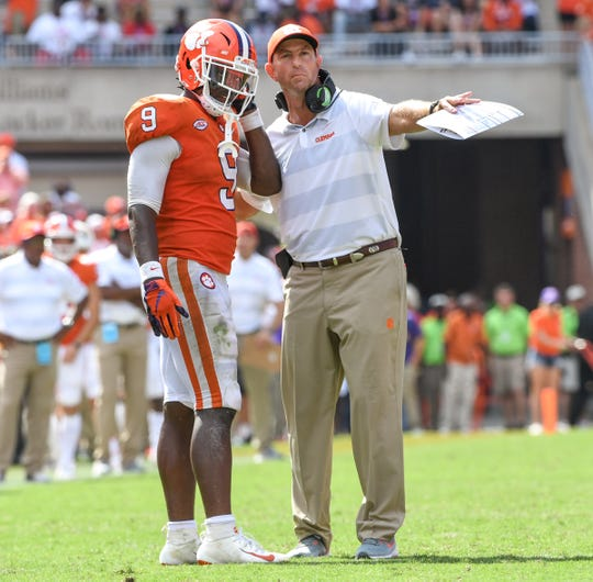 Clemson Head Coach Dabo Swinney talks to Clemson running back Travis Etienne (9) before he scored the winning touchdown against Syracuse during the fourth quarter in Memorial Stadium on Saturday, September 29, 2018.