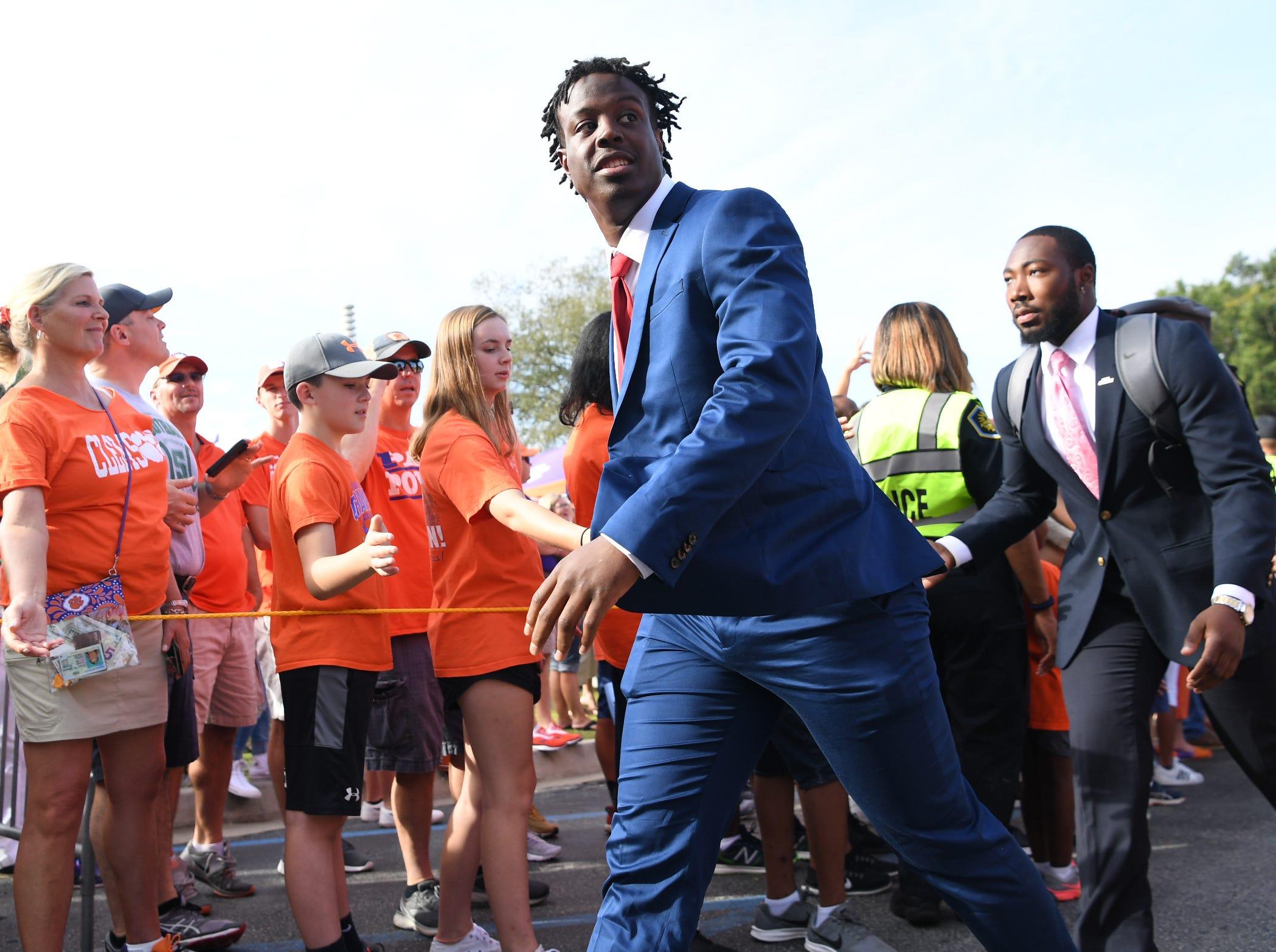 Clemson running back Travis Etienne (9) walks through fans toward Memorial Stadium during Tiger Walk in Clemson on Saturday, September 29, 2018.