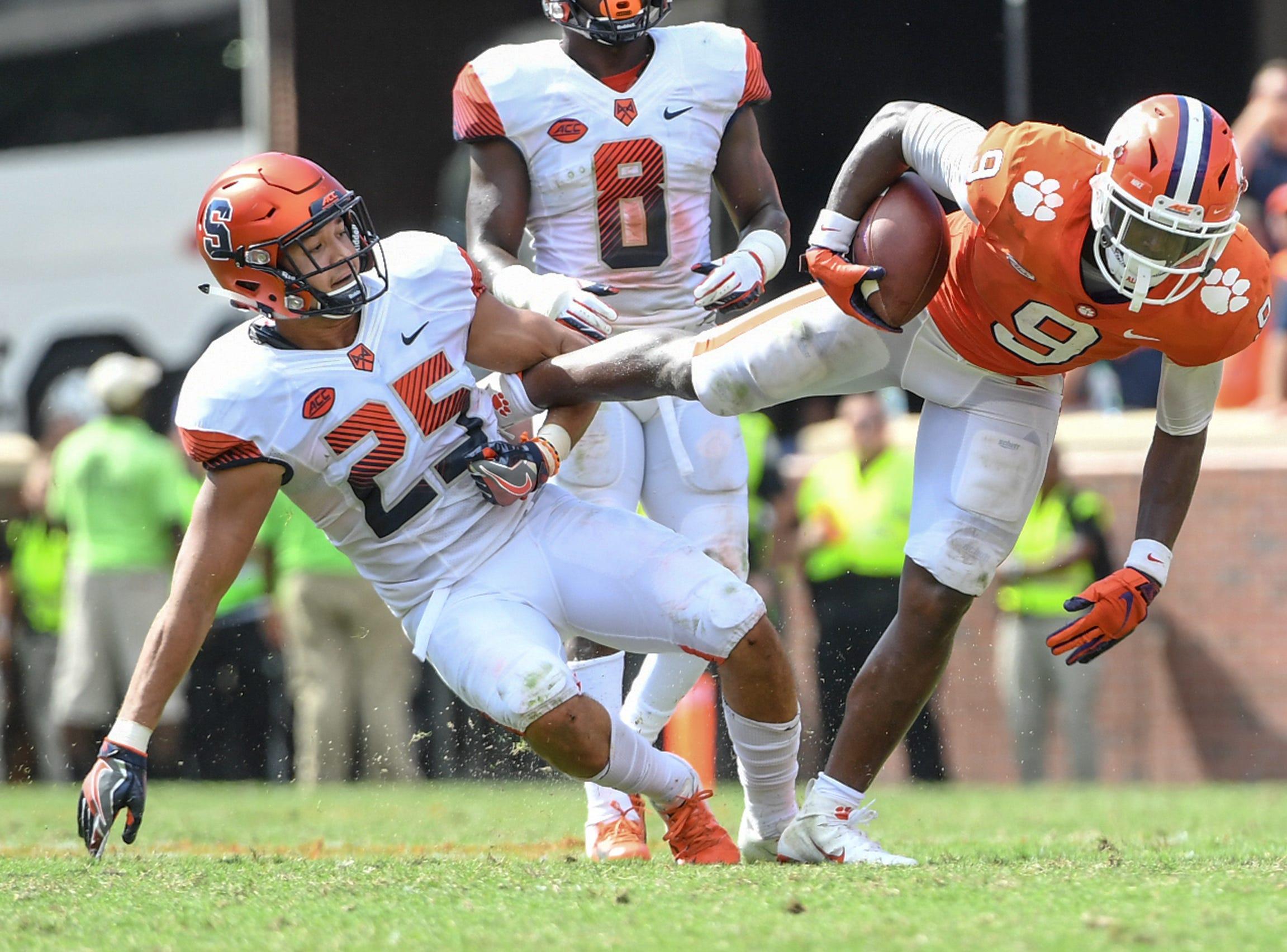 Syracuse linebacker Kielan Whitner(25) holds the foot of Clemson running back Travis Etienne (9) during the fourth quarter in Memorial Stadium on Saturday, September 29, 2018.