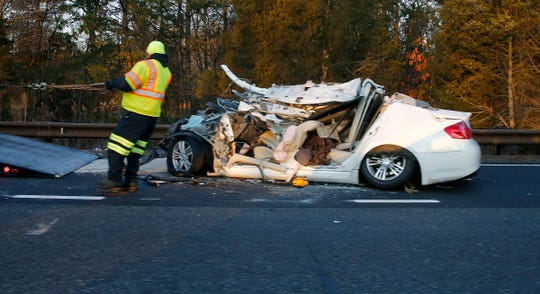 A tow truck operator prepares to hook up a car that crashed into a tanker truck near milepost 81 on the Garden State Parkway Wednesday, December 26, 2018.  State Police confirm that 4 people in the car were killed.