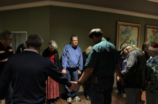 Singers representing various Abilene Church meet Thursday evenings at Hendrick Hospice Care Center and pray before beginning their room-to-room ministry. Leading the prayer Dec. 20 was Jim Nichols, center.