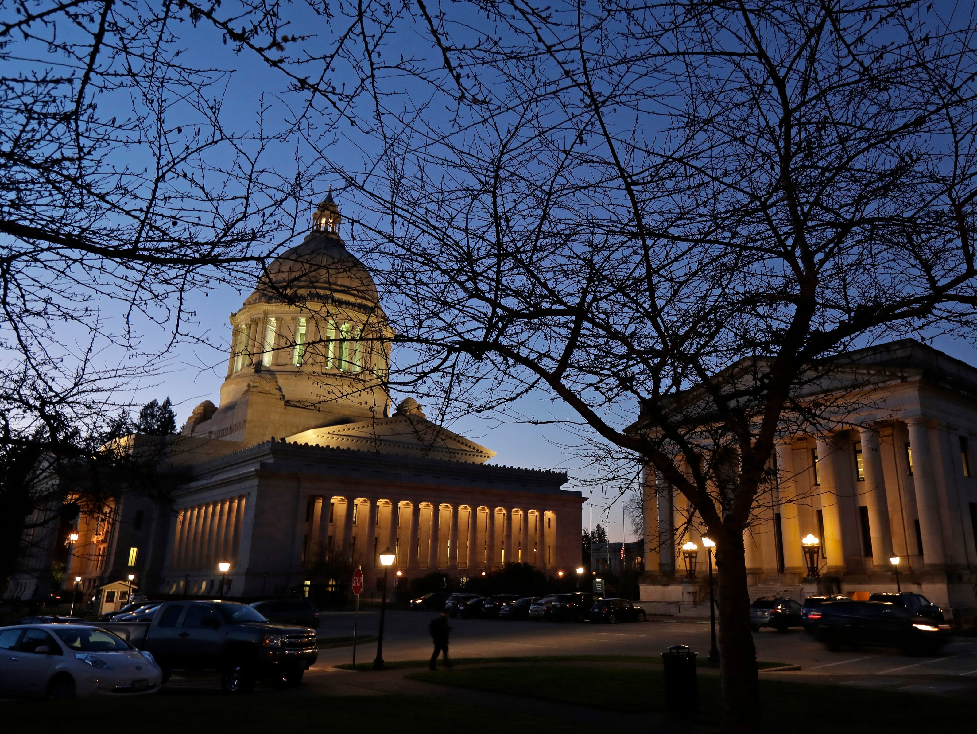 This Dec. 4, 2018, photo, shows the Legislative, left, and Insurance buildings at dusk at the Capitol in Olympia, Wash. In March 2018, following a public outcry, Gov. Jay Inslee vetoed a bill that sought to exempt Washington lawmakers from the state's Public Records Act, which would have allowed lawmakers to shield records sought by a coalition of media groups, led by The Associated Press, who mostly prevailed in a lawsuit. The story was among the state's top news stories of 2018. (AP Photo/Ted S. Warren)