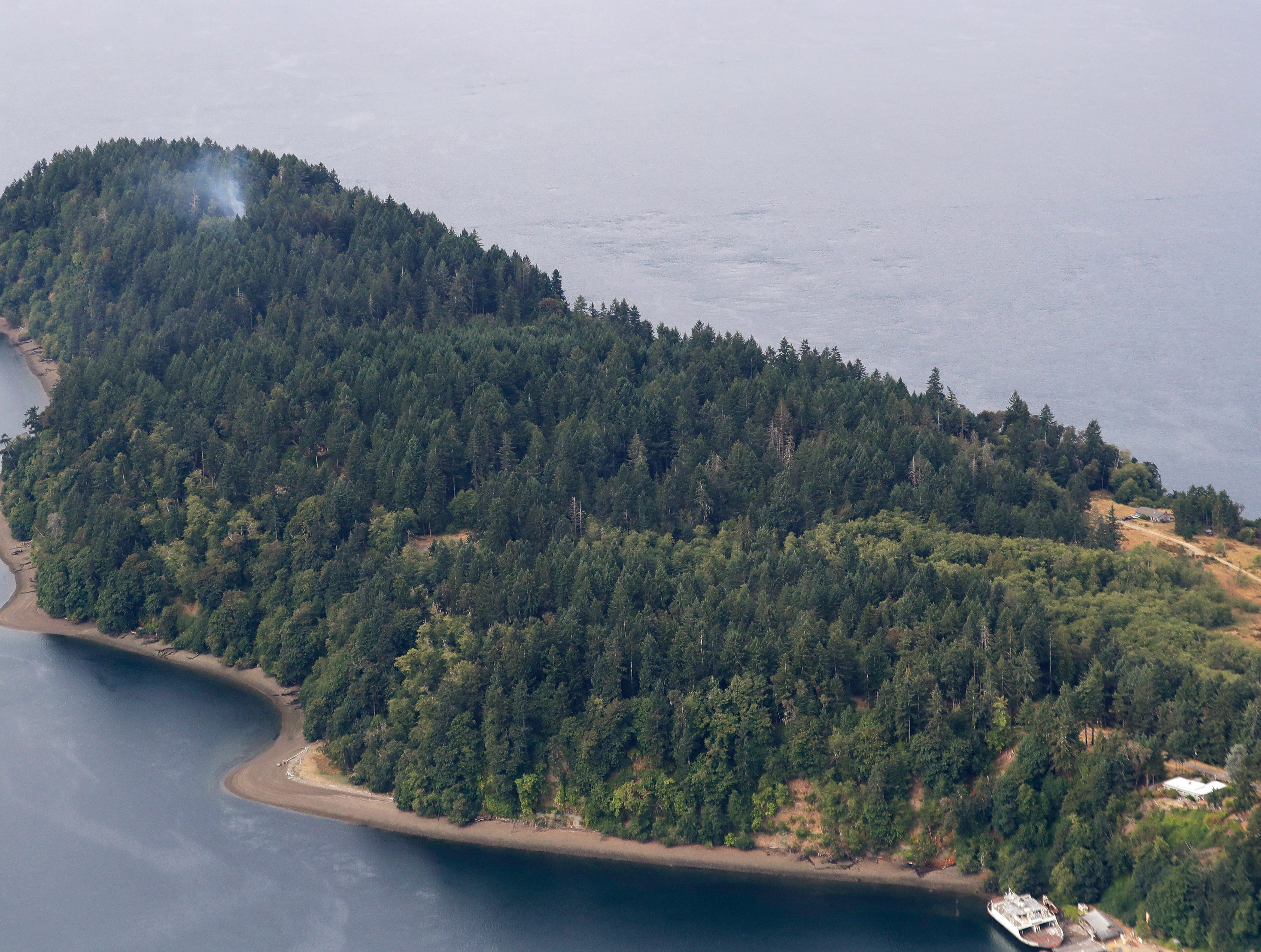 FILE - In this Aug. 11, 2018, file photo, smoke rises from the site on Ketron Island in Washington state where a Horizon Air turboprop plane crashed after it was stolen from Sea-Tac International Airport, as seen from the air near Steilacoom, Wash. The story was voted among the state's top news stories of 2018 by Associated Press staff and member editors. (AP Photo/Ted S. Warren, File)