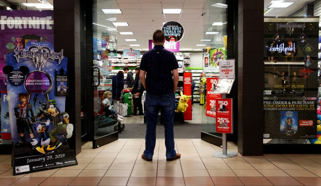 "In this Dec. 9, 2018 photo, a 27-year-old self-described tech addict poses for a portrait in front of a video game store at a mall in Everett, Wash. He asked to remain anonymous because he works in the tech industry and fears that speaking out about the negatives of excessive tech use could hurt his career. ""If we get to a point in the tech industry where I can use my name and show my face in cases like this, thence've gotten somewhere. That'll be a turning point."" (AP Photo/Martha Irvine)"