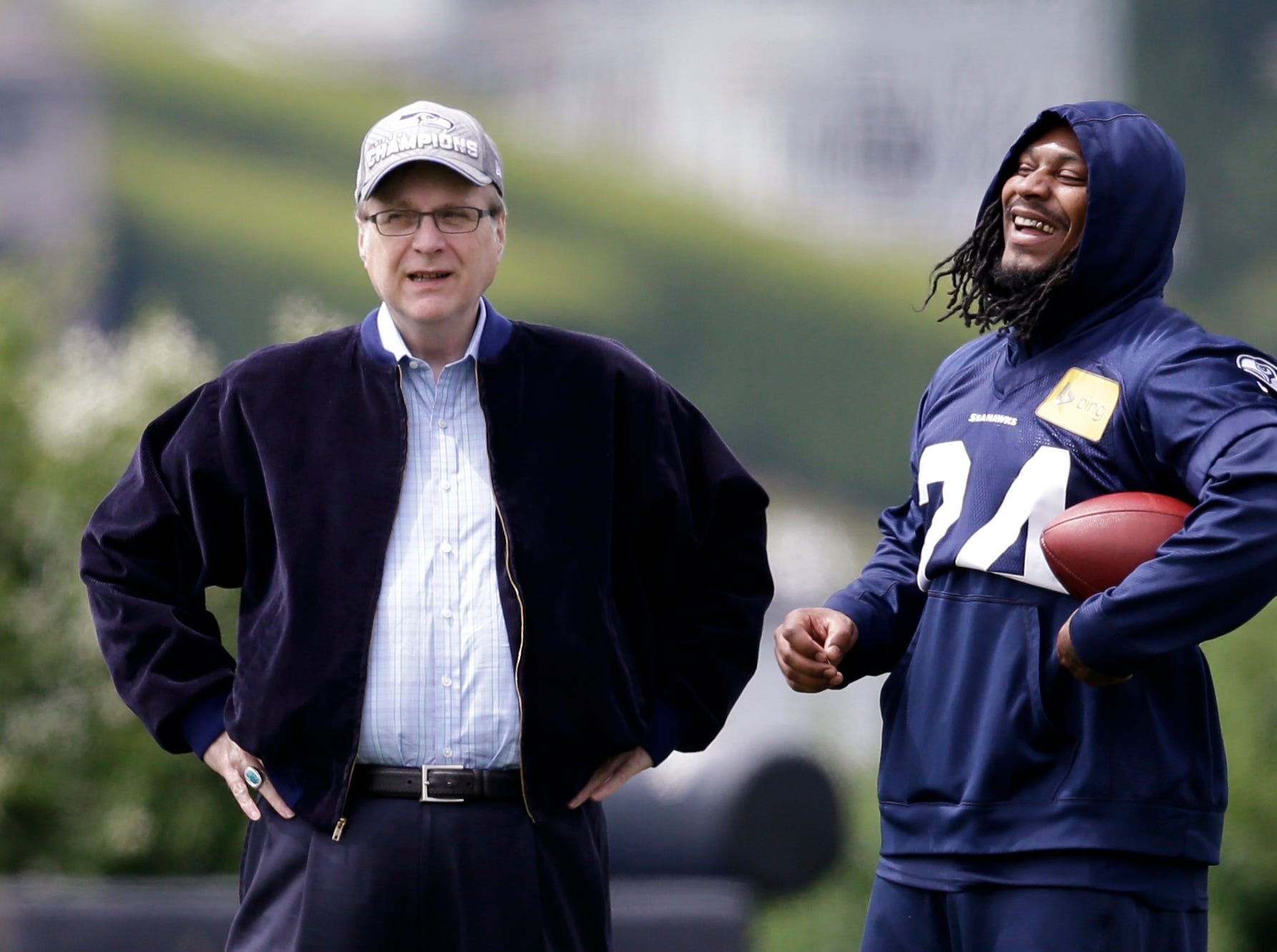 FILE - In this June 18, 2018, file photo, Seattle Seahawks owner Paul Allen, left, talks with running back Marshawn Lynch on the sidelines at an NFL football minicamp practice in Renton, Wash. Paul G. Allen, who co-founded Microsoft with his childhood friend Bill Gates before becoming a billionaire philanthropist, technology investor and owner of the Seattle Seahawks, died in October. Allen's death was among the state's top news stories of 2018. (AP Photo/Elaine Thompson, File)