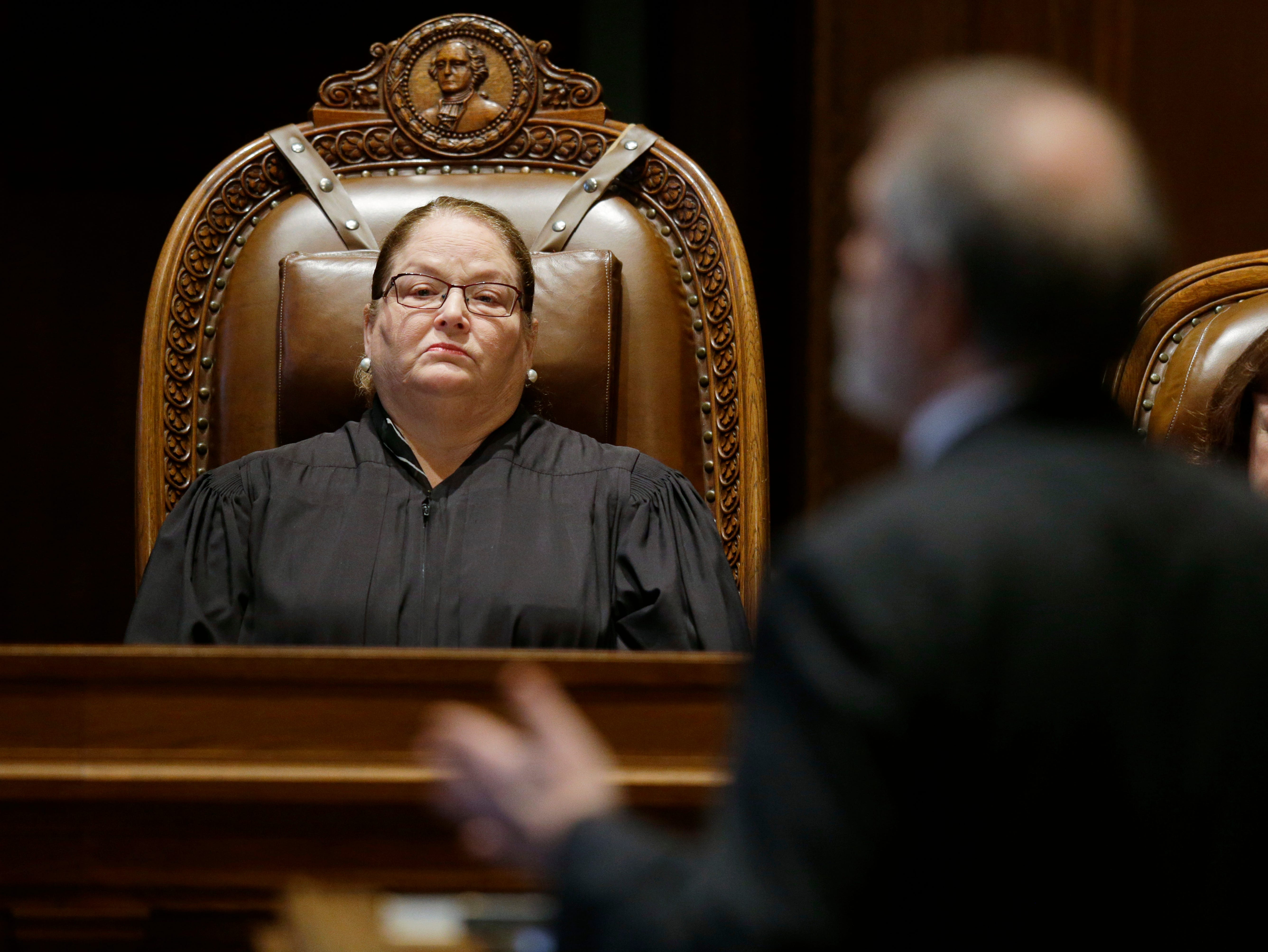 FILE - In this Oct. 24, 2017, file photo, Washington state Supreme Court Chief Justice Mary Fairhurst, left, listens as Alan Copsey, right, deputy solicitor general in the Washington state attorney general's office, speaks during a Washington Supreme Court hearing in Olympia, Wash., addressing the issue of education funding. In June 2018, the Court said lawmakers had successfully finalized the long-running case on state funding of basic education and that the high court would no longer retain jurisdiction in the case, putting it among the state's top news stories of 2018. (AP Photo/Ted S. Warren, File)