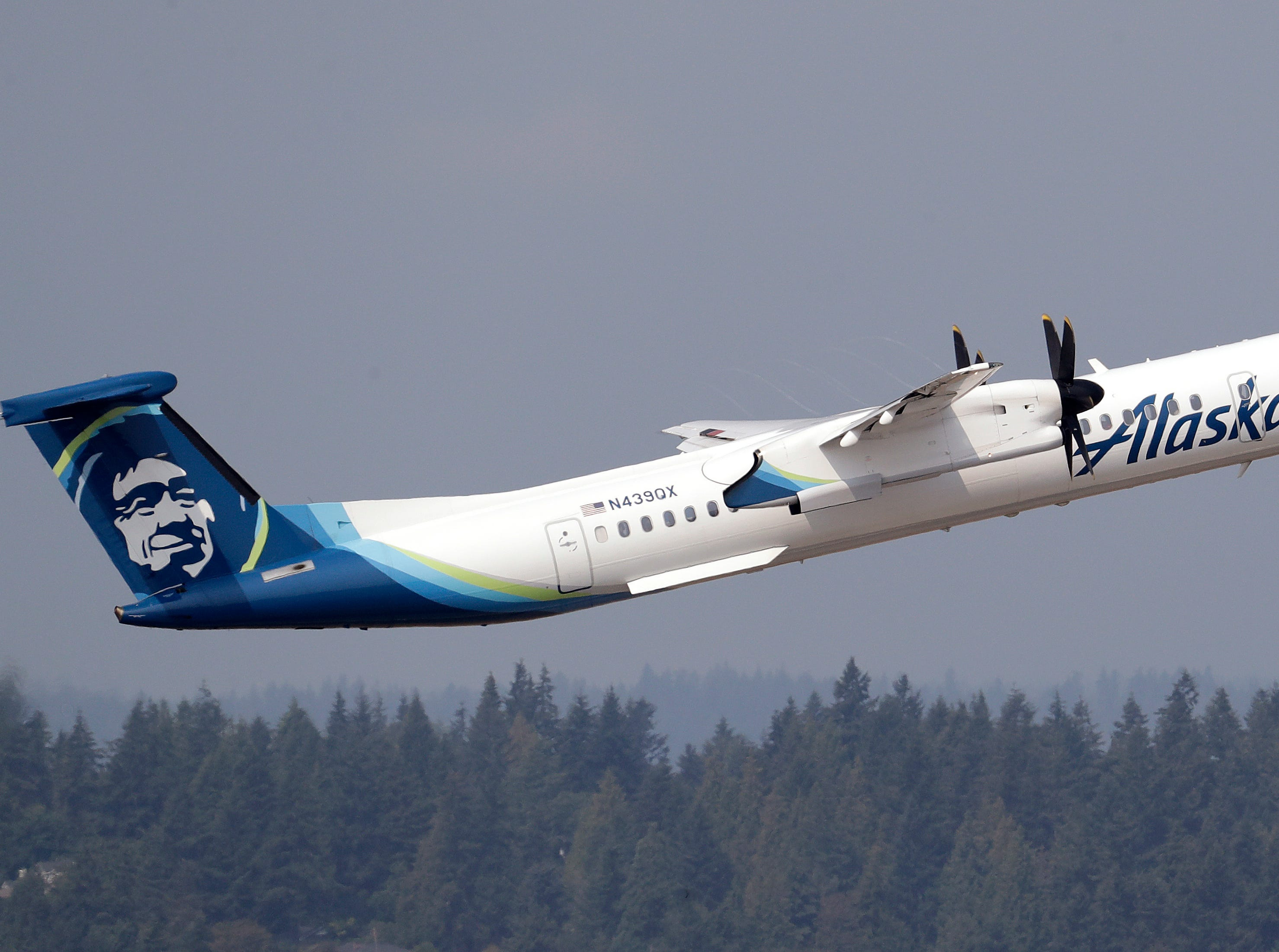 FILE - In this Aug. 13, 2018, file photo, a Horizon Air Q400 turboprop airplane, part of Alaska Air Group, takes off from Seattle-Tacoma International Airport, in SeaTac, Wash. The plane is the same model of aircraft stolen from the airport by an airline ground agent days earlier, which later crashed into a small island in the Puget Sound, killing the man. The story was voted among the state's top news stories of 2018 by Associated Press staff and member editors. (AP Photo/Elaine Thompson, File)