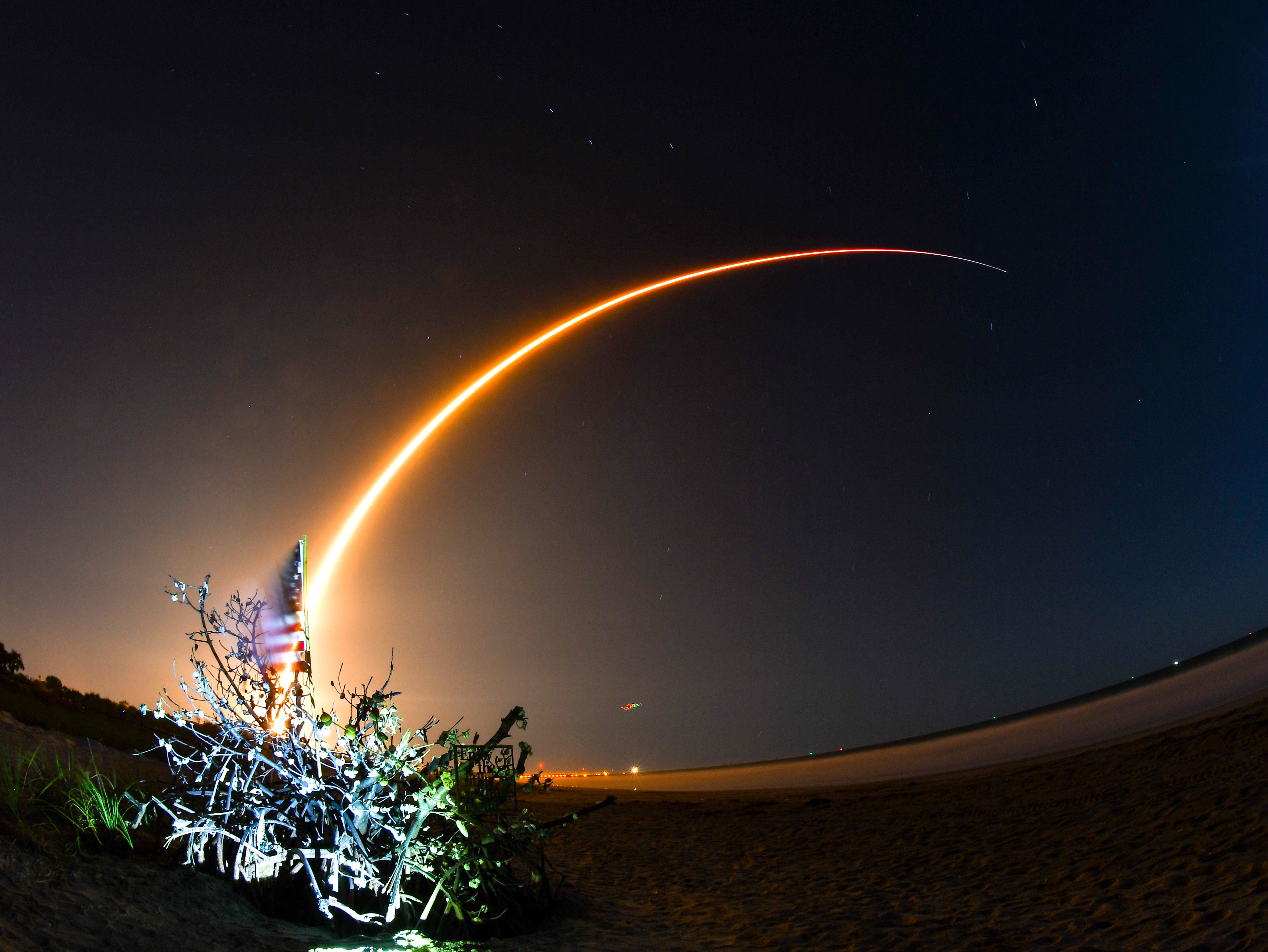 In the foreground is the landmark shell tree, in the sky a time exposure of the SpaceX rocket and the moon. The SpaceX launch of a  Falcon 9 rocket from Complex 40 at Cape Canaveral Air Force Station with a commercial communications satellite early Tuesday morning at 12:33 a.m. The satellite, known as Hispasat 30W-6, is a 12,000-pound spacecraft that will provide television, broadband and other communications services to the Americas and Europe.