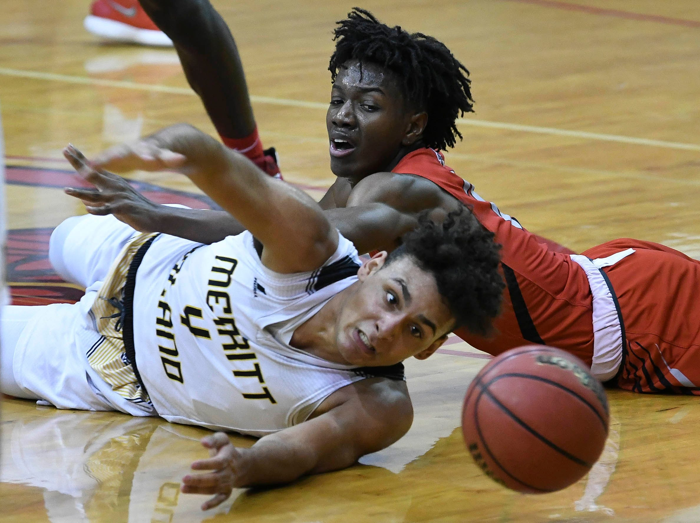 Tyus Echols of Merritt Island and BJ Forbes of Palm Bay chase a loose ball during Tuesday's District 14-6A basketball playoff game
