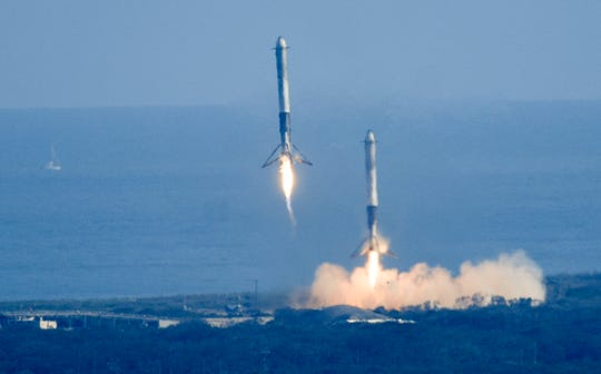 The twin boosters from SpaceX's newest rocket, the Falcon Heavy make a successful landing at Landing Zone 1 at Cape Canaveral Air Force Station. Mandatory Credit: Craig Bailey/FLORIDA TODAY via USA TODAY NETWORK