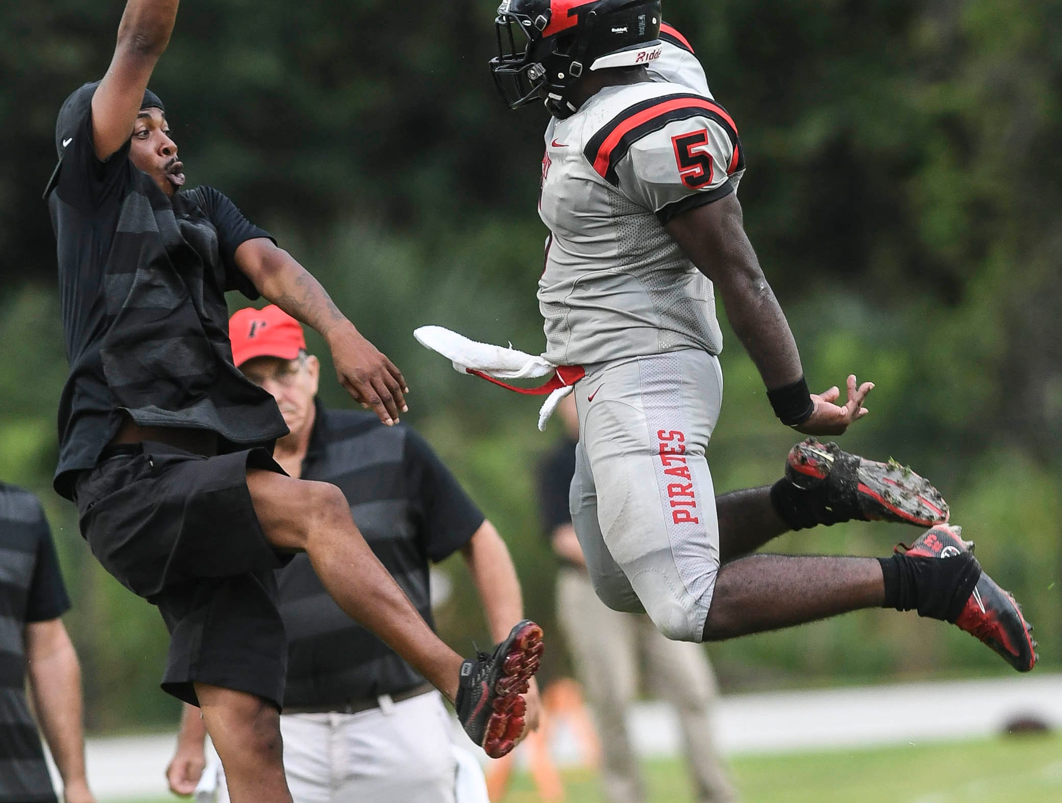 Negail Wright celebrates a TD with a Palm Bay assistant coach during Friday's game.