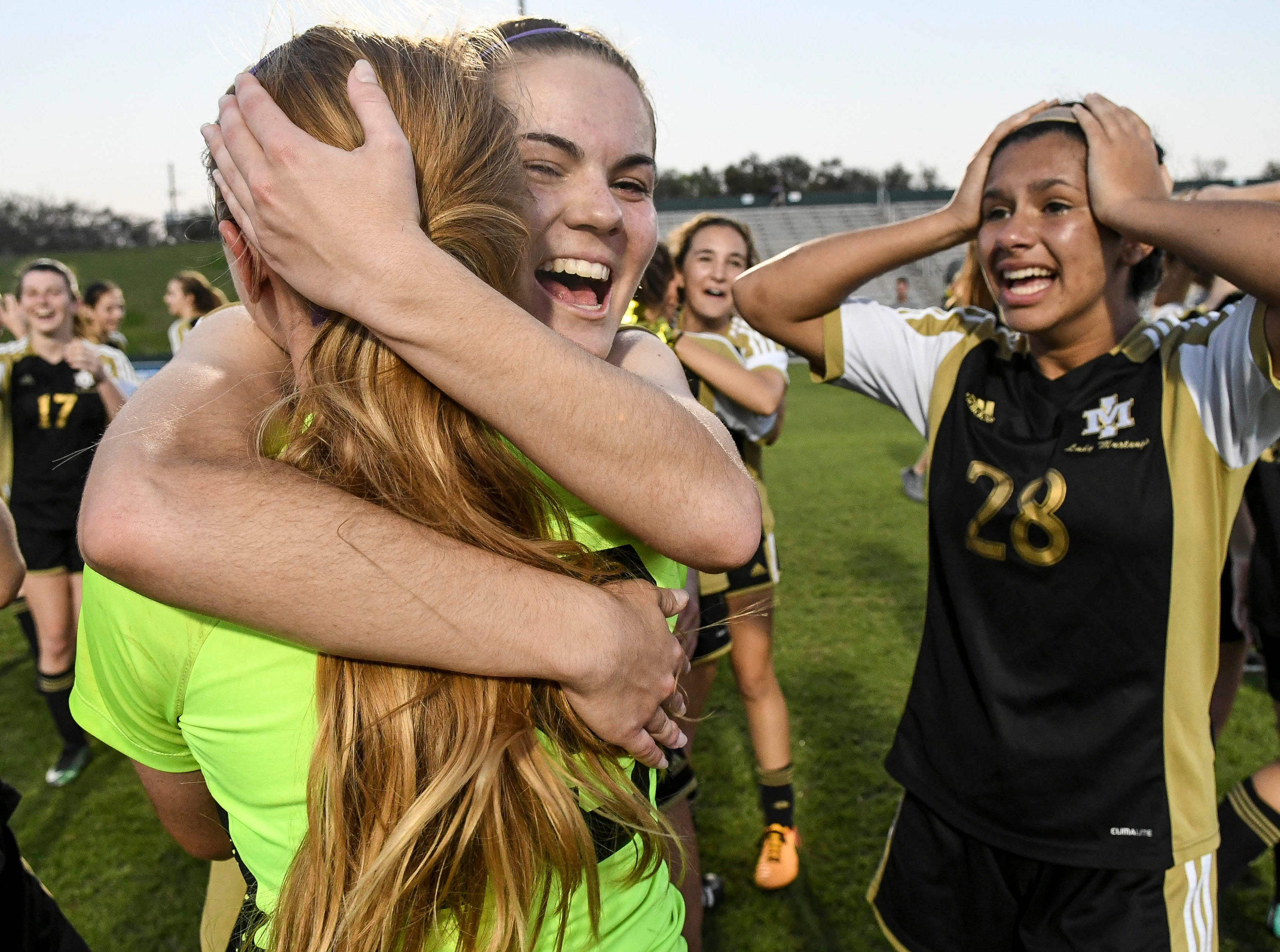 Merritt Island players Samantha Parker, Jordan Tomberlin and Amaya Quintal celebrate the Mustangs' Class 3A soccer title Friday in Deland.