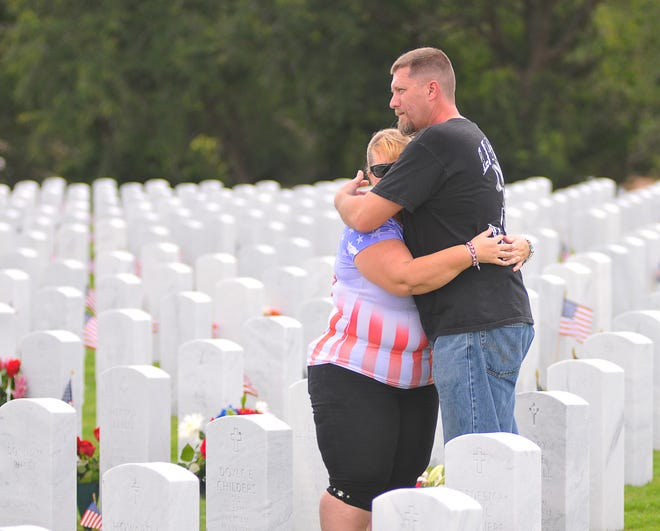 Diana Anderson gets a hug from Chris Moak during the 2018 Memorial Day Observance at the Canaveral National Cemetery in Mims. The Geneva couple visited Anderson's father's grave after the ceremony.