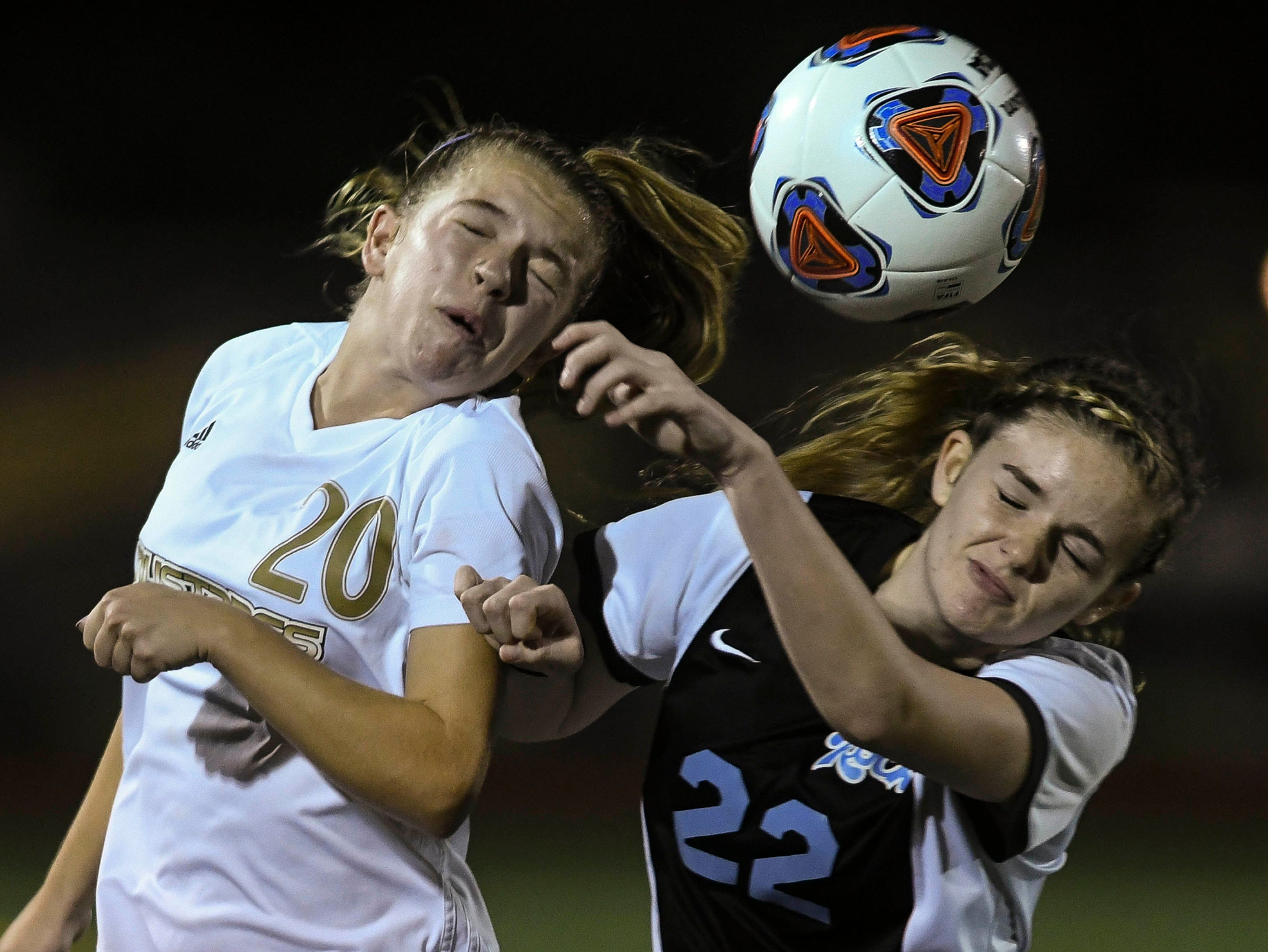 Sydney Clark of Merritt Island (20) and Leena Hungerbuhler try to head the ball during Friday's egional semifinal game.