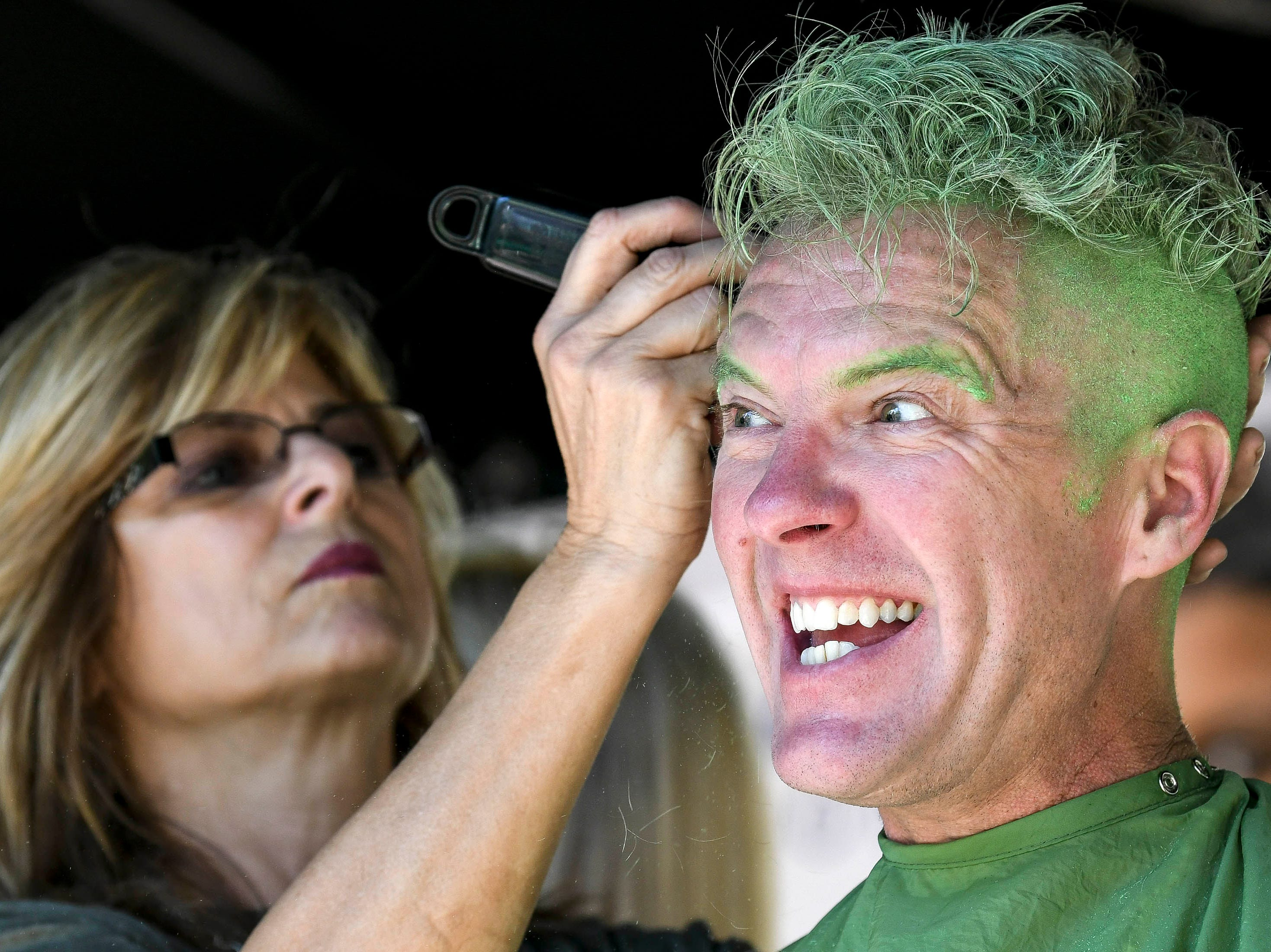 Scott Schmidt reacts to having his head shaved by Renee Dippel of Ambiance Salon and Spa during the St. Baldricks Foundation fundraiser at the Avenue Viera.