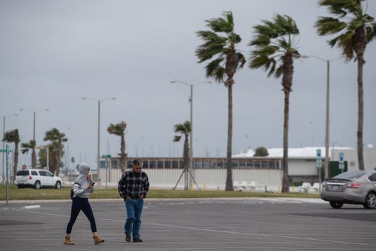 Two people walk thought a parking lot near the Bayfront in downtown Corpus Christi as a cold front blows in on Wednesday, Dec. 26, 201`8.