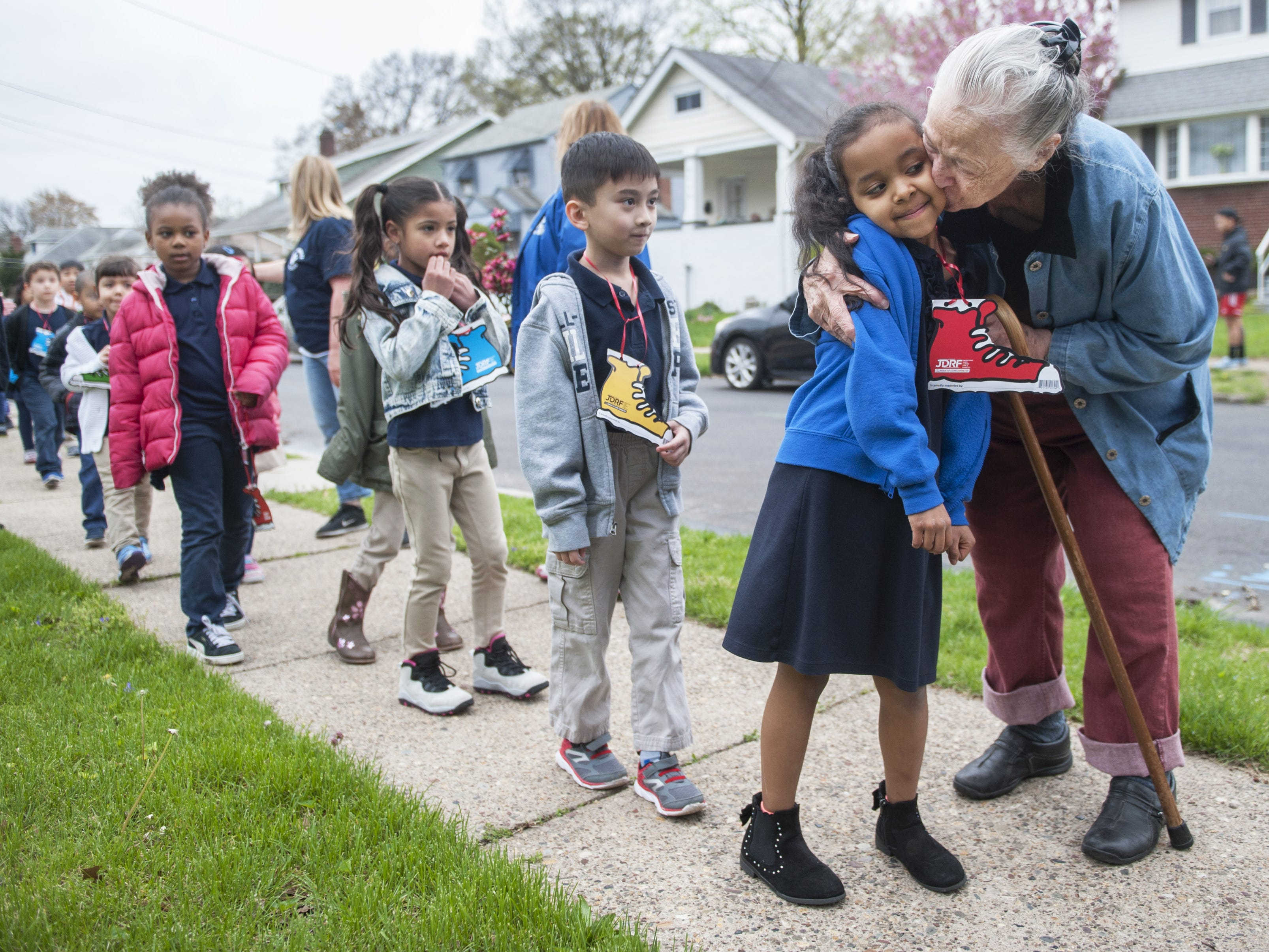 Retired school crossing guard Laura Mason, right, hugs and kisses students of Roosevelt Elementary School in Pennsauken as the students made a surprise visit to Mason's Pennsauken home, during the school's Walk To Cure Diabetes on April 27, 2018, to thank Mason for her 50 years of service as a crossing guard.