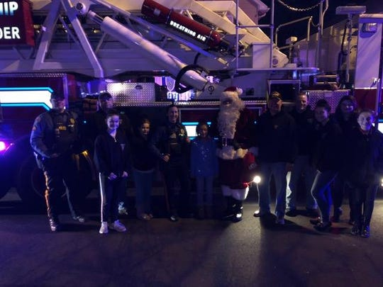 Santa and Florence Township Police officers spend part of Christmas Eve with a family whose car was stolen on Saturday. The vehicle had been filled with most of the family's holiday gifts.