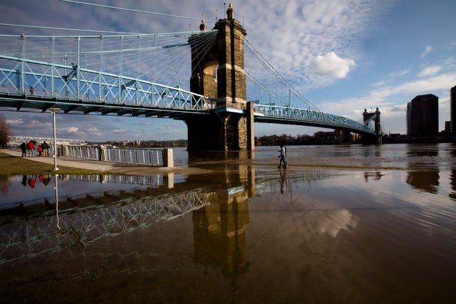 Pedestrians walk on the Ohio River Trail Smale Riverfront Park in Downtown Cincinnati on Tuesday, Dec. 25, 2018. The National Weather Service has placed the area under a flood warning until Wednesday, Dec. 26, at 1 p.m.