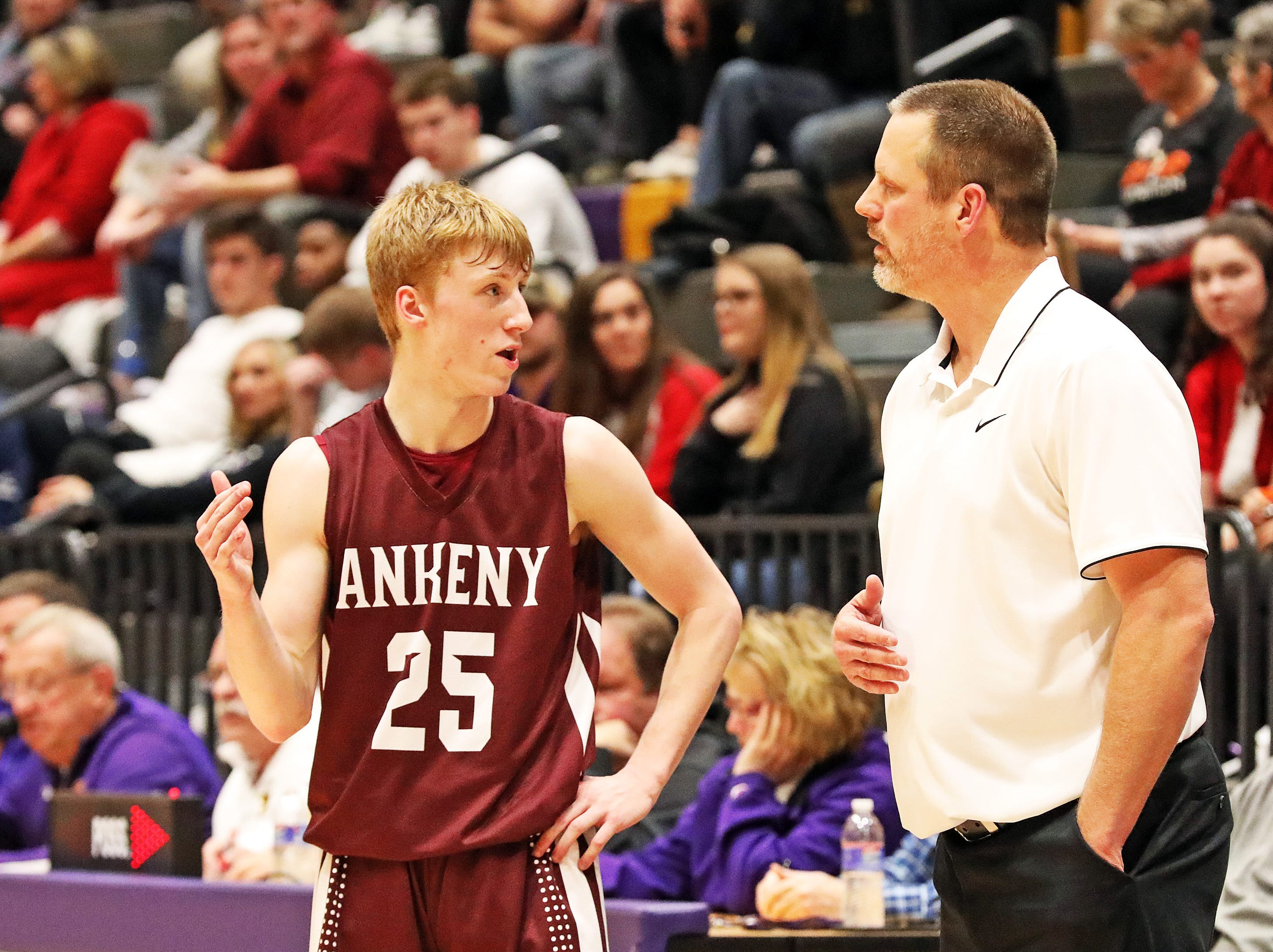 Ankeny senior Dillon Carlson plans the next play with his Dad and head coach Brandt Carlson as the Ankeny Hawks compete against the Johnston Dragons in high school basketball on Friday, Dec. 21, 2018 at Johnston High School.