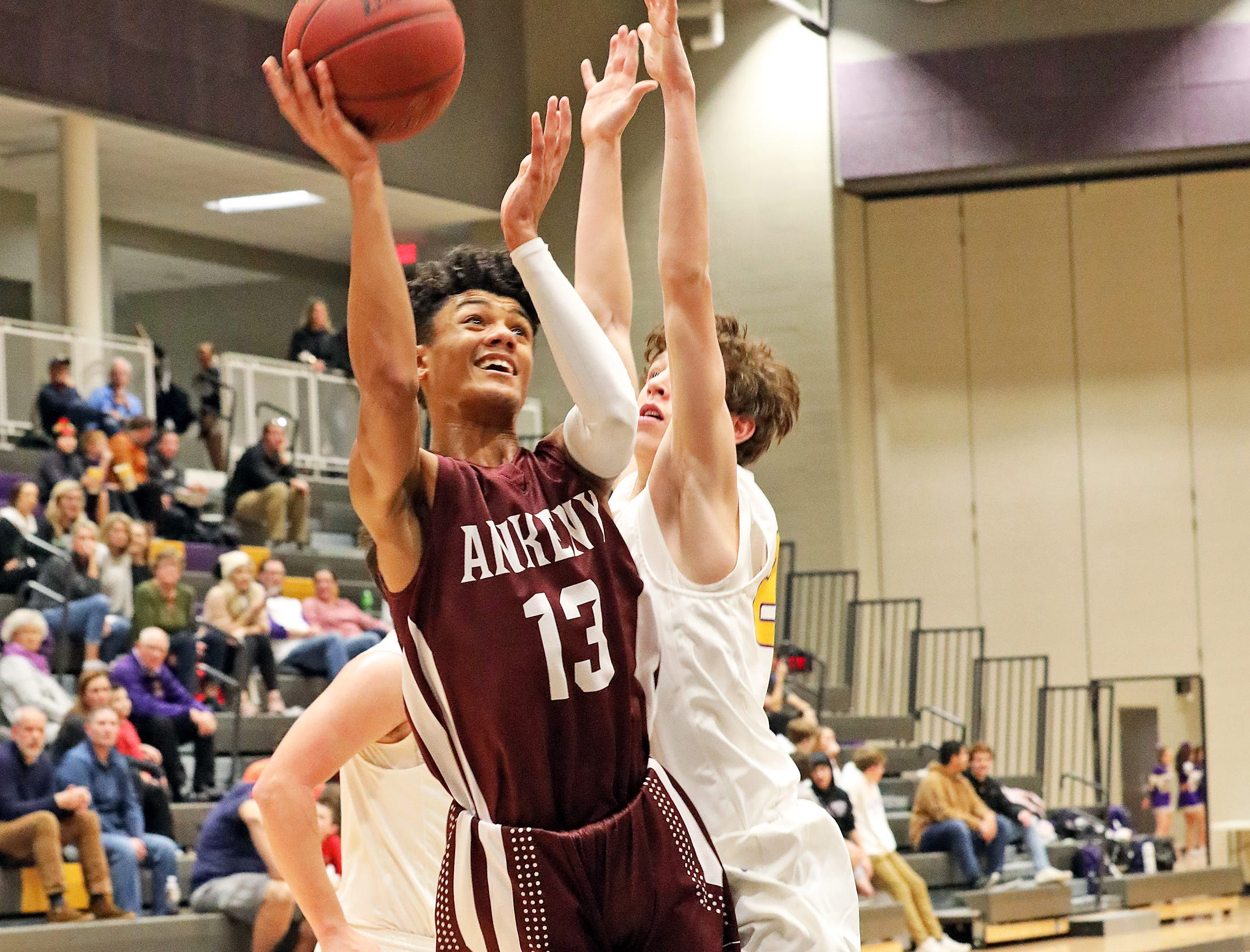 Ankeny junior Jaxon Smith shoots past the tough defense as the Ankeny Hawks compete against the Johnston Dragons in high school basketball on Friday, Dec. 21, 2018 at Johnston High School.
