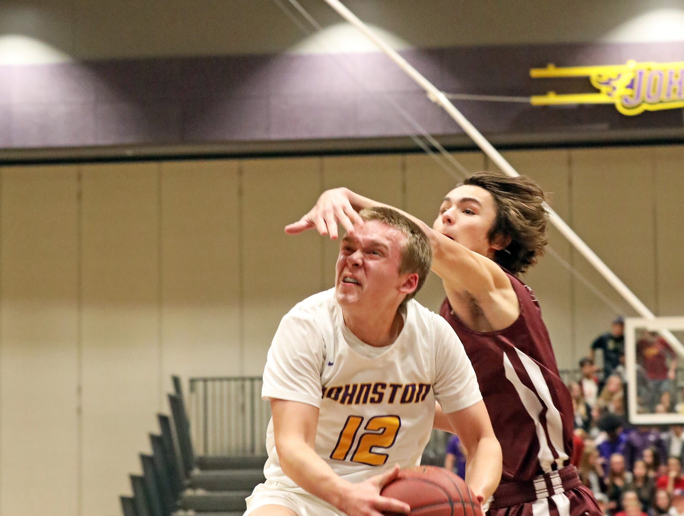 Johnston freshman Jacob Runyan drives against the tough defense as the Ankeny Hawks compete against the Johnston Dragons in high school basketball on Friday, Dec. 21, 2018 at Johnston High School.