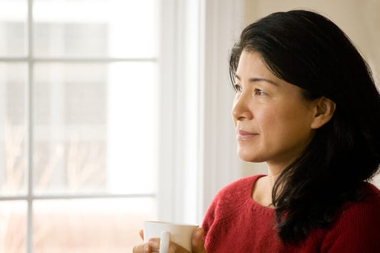 Pensive Mature Asian Woman At Window Holding Cup Of Tea