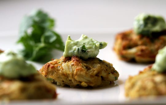 Miniature crab cakes with avocado dip.