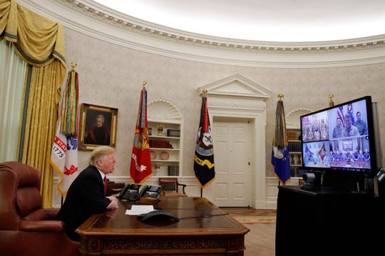 President Donald Trump greets members of the five branches of the military via video conference on Christmas Day, Tuesday, Dec. 25, 2018, in the Oval Office of the White House. The military members were stationed in Guam, Qatar, Alaska, and two in Bahrain.