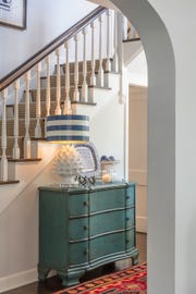 Placing a chest of drawers in a hallway offers you a spot to put a welcoming lamp and a few fun accents. (BOB GREENSPAN)