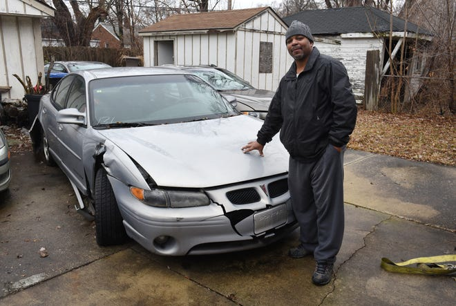 Gerald Grays of Detroit shows the damage to his 2000 Pontiac Grand Prix, which he reported stolen two years ago.  He filed suit against the city and Bobby's Towing to dispute the towing and storage charges.