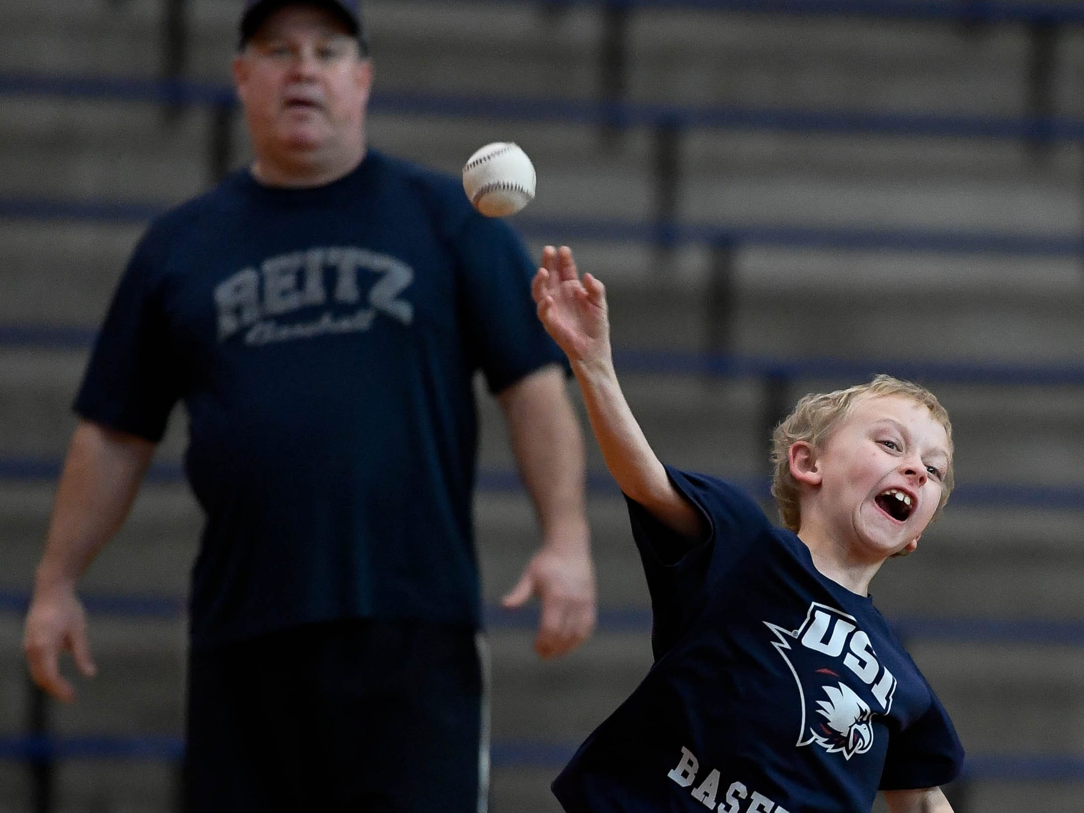 Reitz baseball head coach Todd DeWeese watches as Parker Hensley, eight years-old, makes a throw toward home plate during fielding practice at the 2018 Reitz Baseball Holiday Camp, for grades 1-7, held at the Reitz gym Wednesday, December 26, 2018.