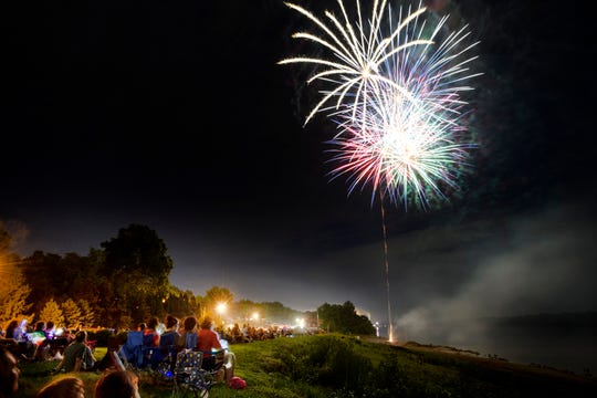 People watch the fireworks show while lounging in the grass near the Ohio River during the Independence Day Celebration at Old Lock & Dam Park in Newburgh, Ind., Tuesday, July 3, 2018. Rain showers hit the area in the afternoon, but ended as the 2018 Historic Newburgh Fireworks and Evening at the Park event kicked off.