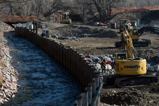 Construction crews move large rocks in the dried riverbed while diverted water runs on the other side of a manmade barricade on Wednesday at the North College Avenue bridge over the Cache la Poudre River in Fort Collins. The area is being made into a whitewater recreational park.