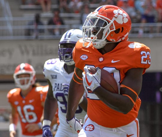Clemson running back Lyn-J Dixon (23) runs near Furman outside linebacker Chris Washington (99) during the third quarter in Memorial Stadium in Clemson on Sept. 1.