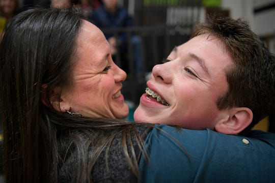 """In this Tuesday, Dec. 18, 2018, photo, Devin McLane and his mother, Michelle hug after McLane's first match on Tuesday night in Corvallis, Mont. """"I've always told him from day one, I'm not going to be doing that up until your 30. You gotta fight, you gotta find your way,"""" Michelle said."""